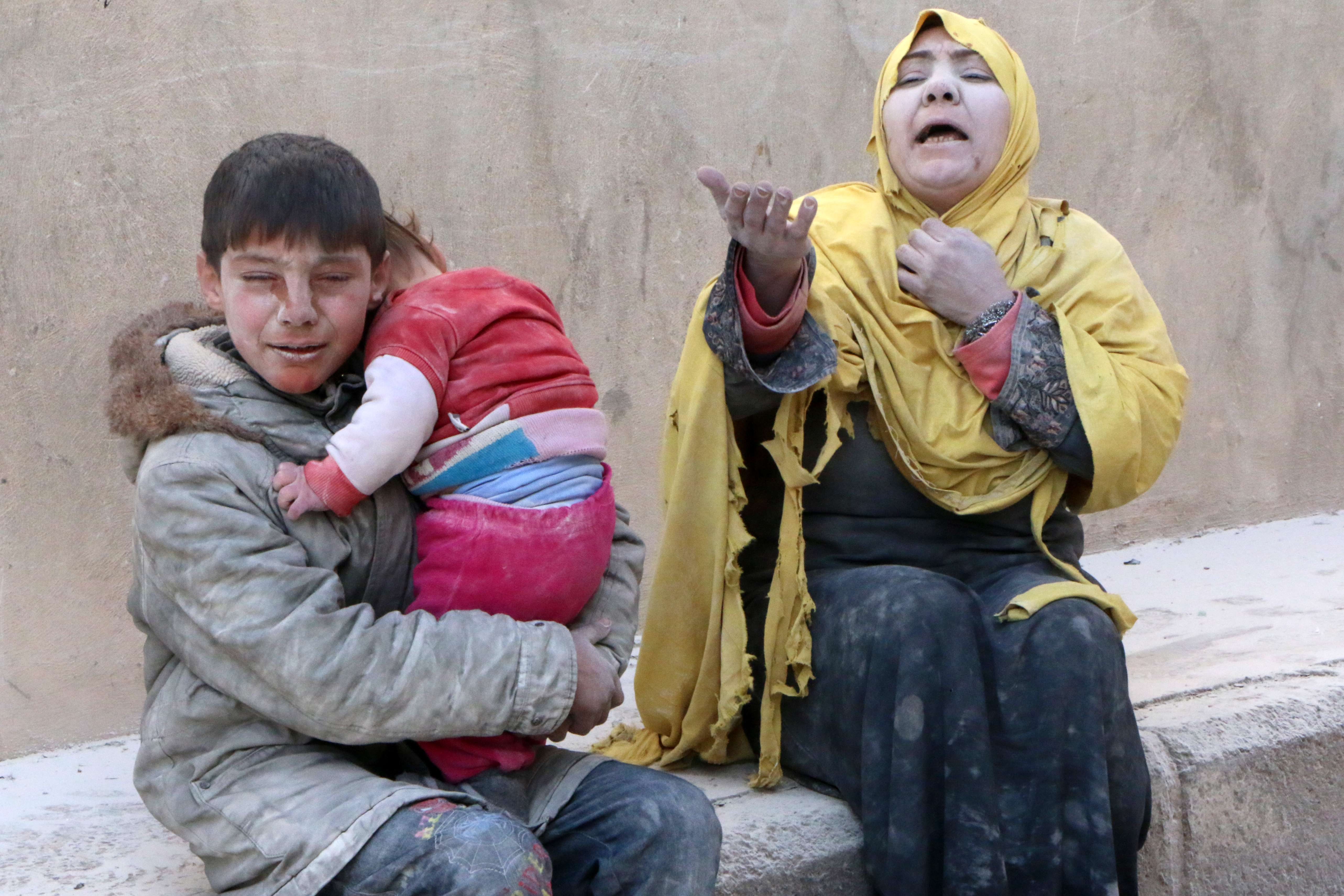 A woman, a young boy and a baby, covered with dust, sit in a state of shock following a reported air strike attack by government forces on the Hanano district of the northern Syrian city of Aleppo on February 14, 2014. Syria's warring sides began what was expected to be a decisive final day of talks in Geneva, amid warnings that they must at least agree an agenda to save the process.    (AFP PHOTO/ALEPPO MEDIA CENTRE/FADI AL-HALABI)