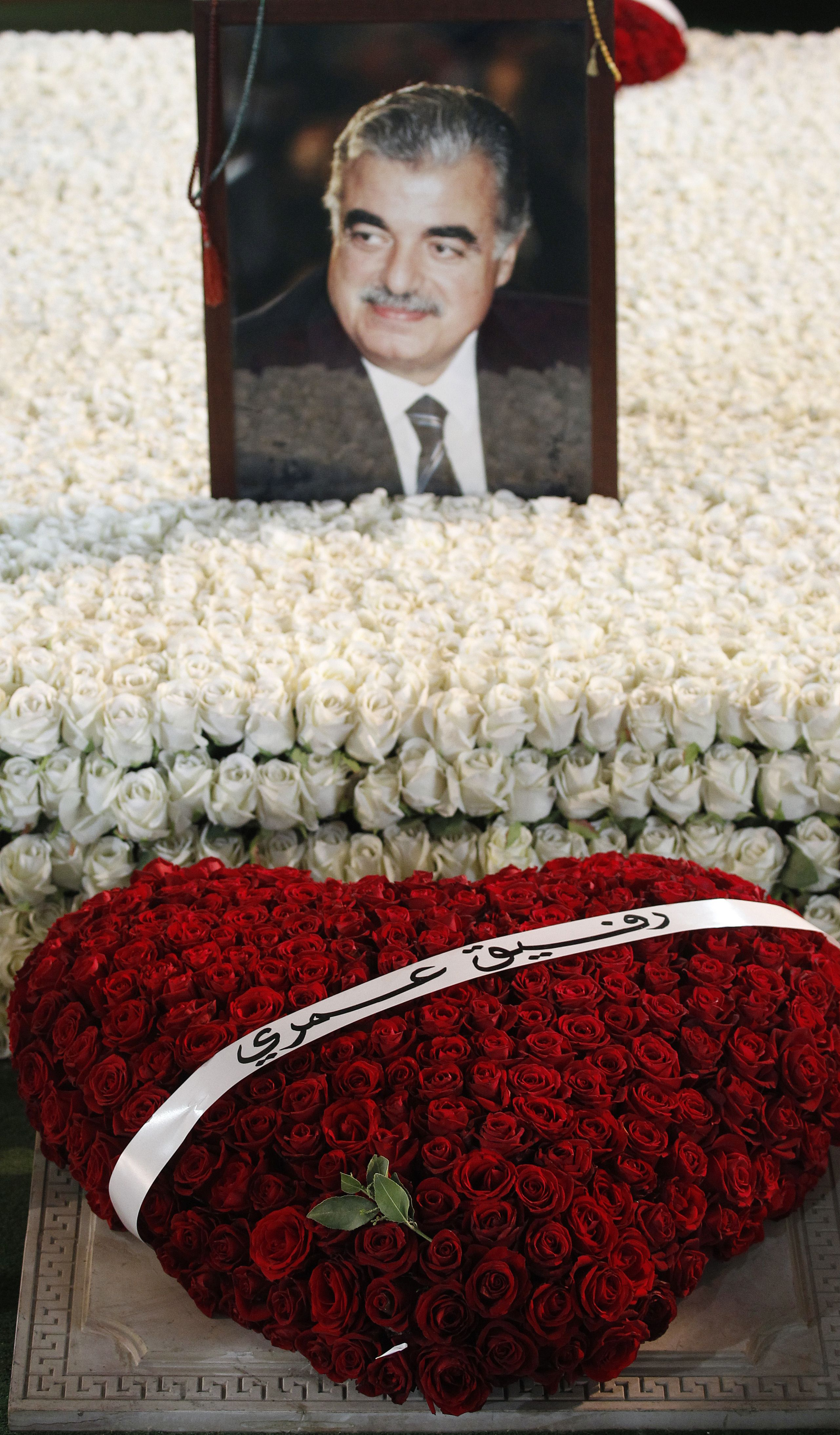 """A heart-shaped red roses bouquet adorns the grave of former Lebenese prime minister Rafiq Hariri (portrait), on the ninth anniversary of his death, in Beirut on February 14, 2014. The wreath was sent by his wife Nazik and reads in Arabic, """"my life partner"""".  (AFP PHOTO/ANWAR AMRO)"""