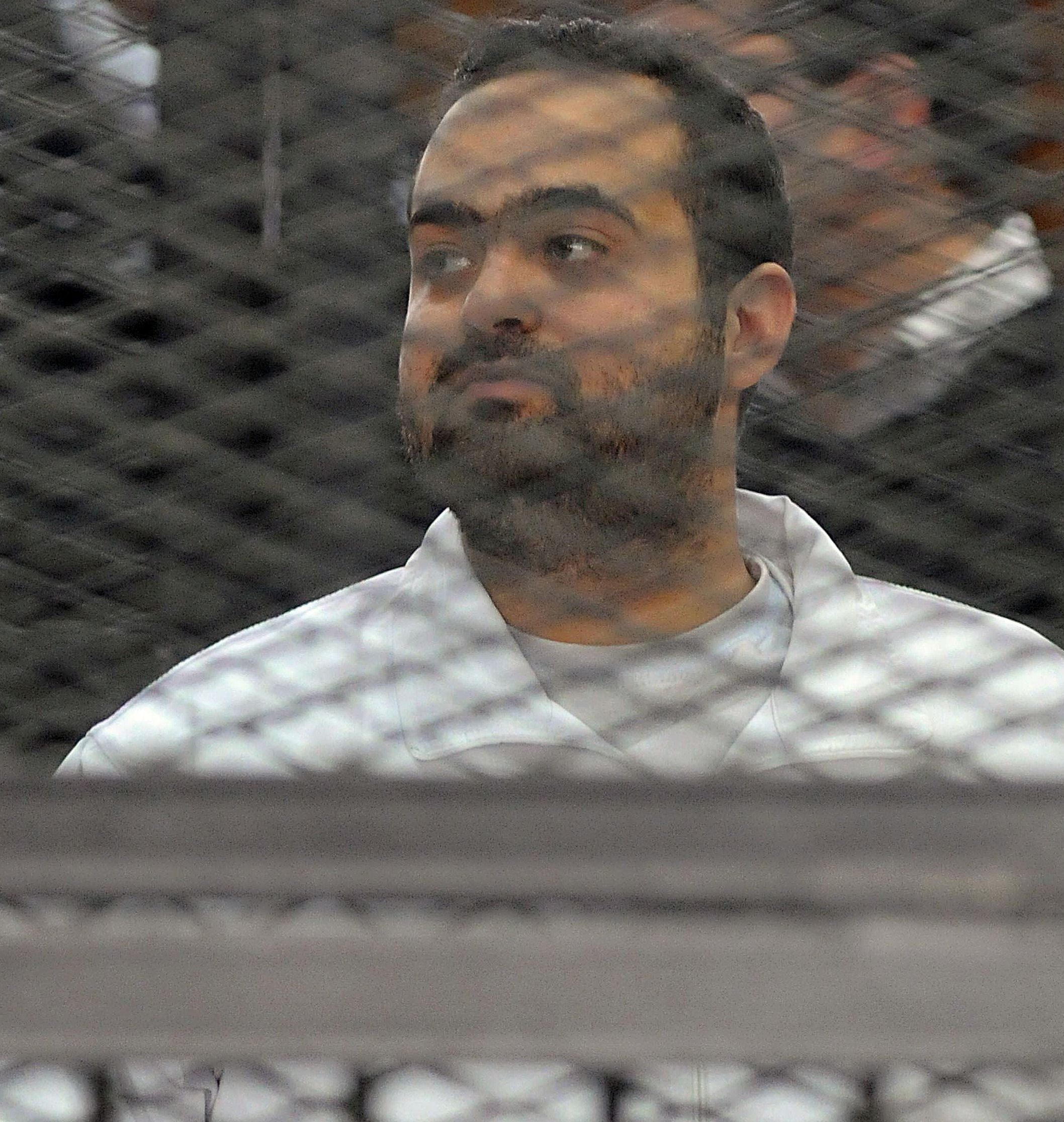 Egyptian prominent activicts Mohamed Adel stands in the accused dock during his trial on December 22, 2013, in Cairo. An Egyptian court sentenced three activists, Mohamed Adel, Ahmed Maher (unseen), the founder of the April 6 youth movement that led the revolt against former president Hosni Mubarak, and Ahmed Douma (unseen), all accused of spearheading the 2011 uprising against Mubarak to three years in jail for organising an unlicensed protest, judicial sources said. It was the first such verdict against non-Islamist protesters since the overthrow of president Mohamed Morsi in July, and was seen by rights groups as part of a widening crackdown on demonstrations by military-installed authorities. AFP PHOTO/STR