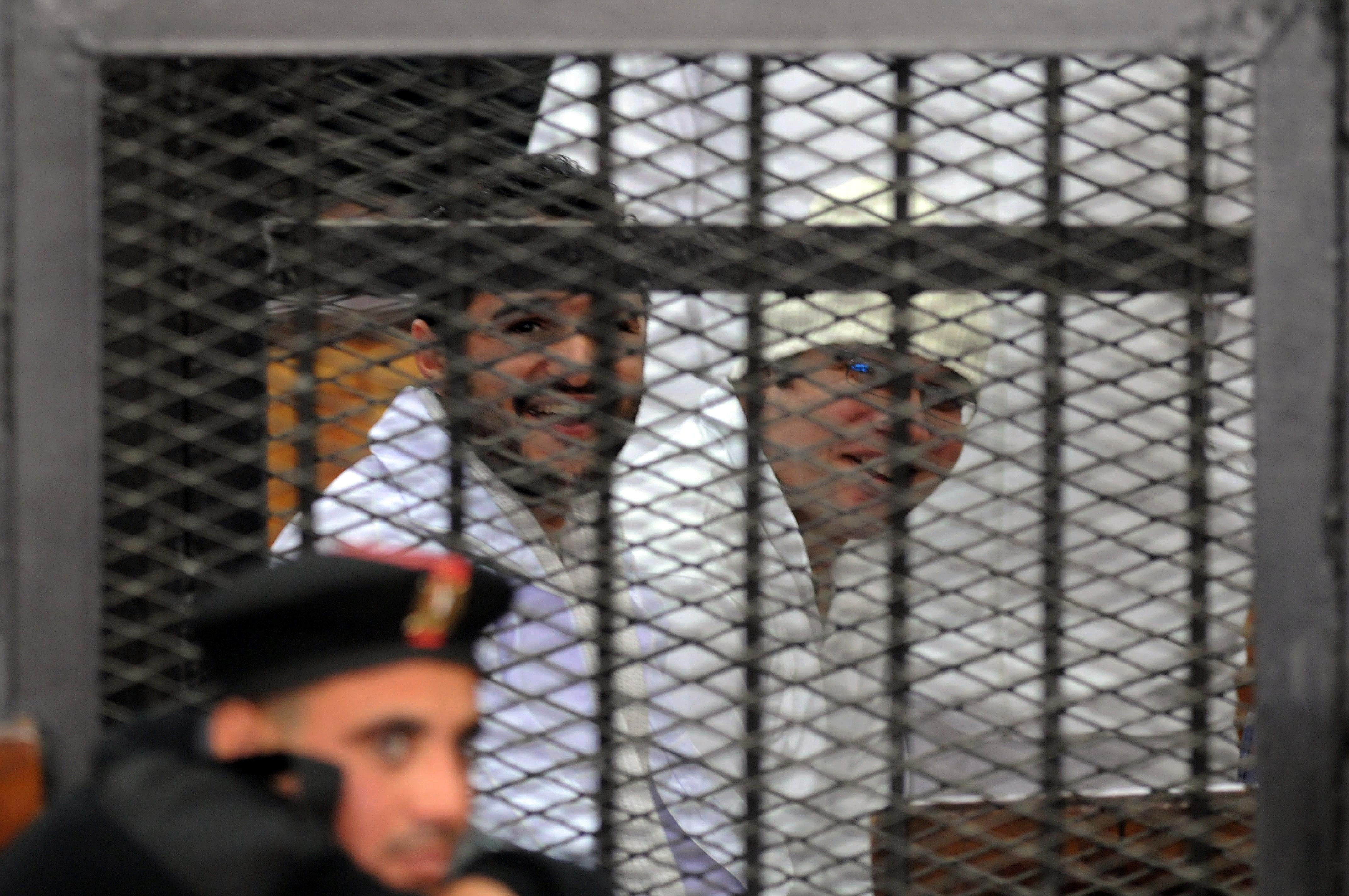 Egyptian prominent activicts Ahmed Douma (L) and Ahmed Maher (R), the founder of the April 6 youth movement that led the revolt against ousted president Hosni Mubarak, as they stand in the accused dock during their trial on December 22, 2013 in Cairo. An Egyptian court sentenced three activists, Douma, Maher and Mohamed Adel, who spearheaded the 2011 uprising against Hosni Mubarak to three years in jail for organising an unlicensed protest, judicial sources said. It was the first such verdict against non-Islamist protesters since the overthrow of president Mohamed Morsi in July, and was seen by rights groups as part of a widening crackdown on demonstrations by military-installed authorities. (AFP PHOTO/STR)