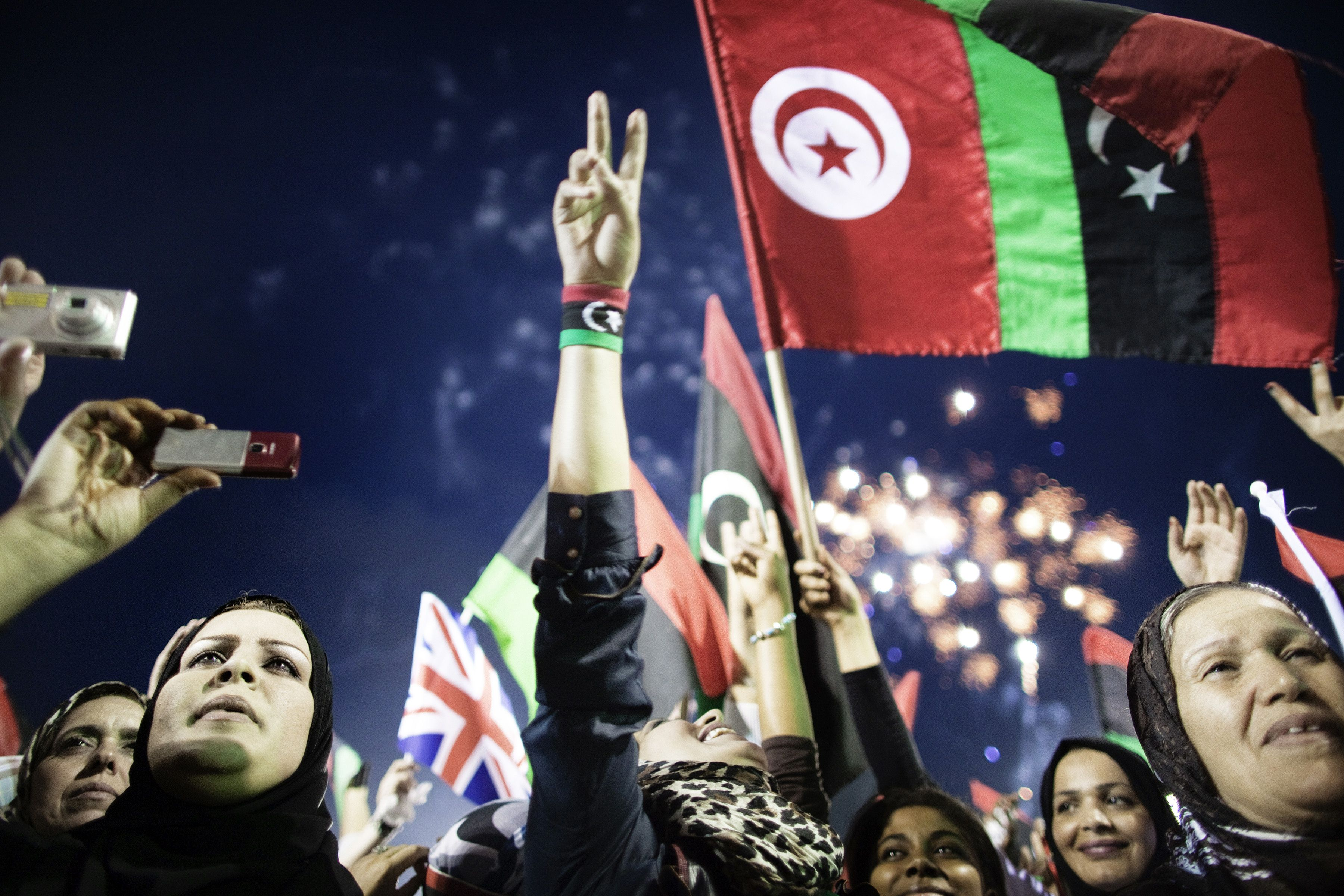 A picture taken on October 23, 2011 shows Libyans celebrating following the announcement of the liberation of the country in Martyr's Square in central Tripoli three days after ousted despot Moamer Kadhafi was captured and killed. As Libya prepares to commemorate three years since the uprising that ousted and killed long-time dictator Moamer Kadhafi on February 17, 2014, the country is haunted by a nightmare of lawlessness that has overshadowed people's dreams of a better life.   (AFP PHOTO/MARCO LONGARI)