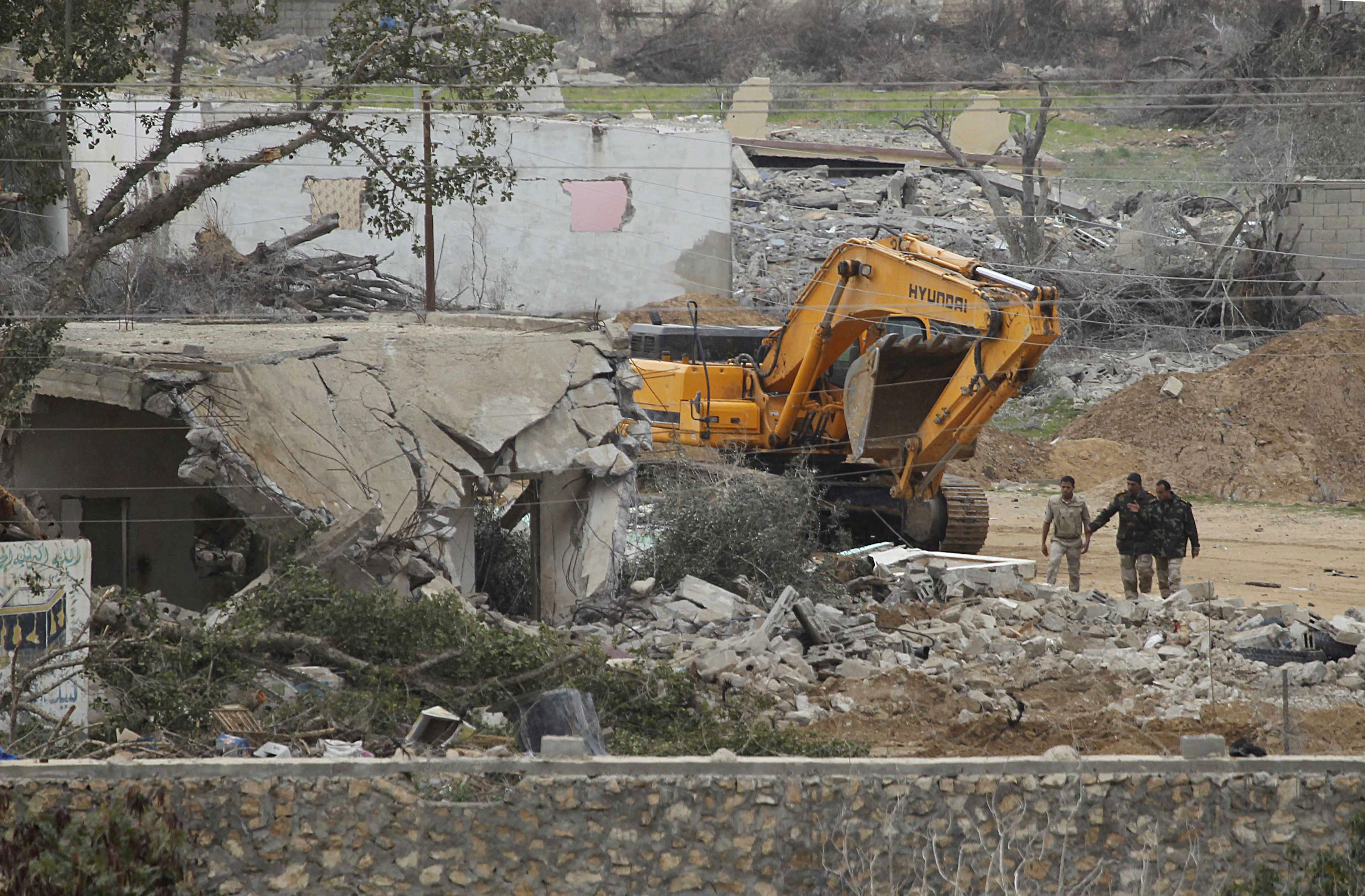 A picture taken from the Southern Gaza Strip shows a mechanical digger used by the Egyptian army in search of tunnels on the border with Egypt and the Gaza Strip on February 15, 2014. Much of the smuggling tunnels were destroyed following the Egyptian military's July 2013 overthrow of Islamist president Mohamed Morsi, seen as a Hamas ally.  (AFP PHOTO / SAID KHATIB)