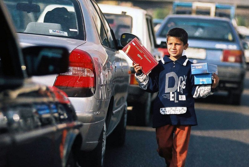 A young child sells tissues in traffic (DNE File photo)