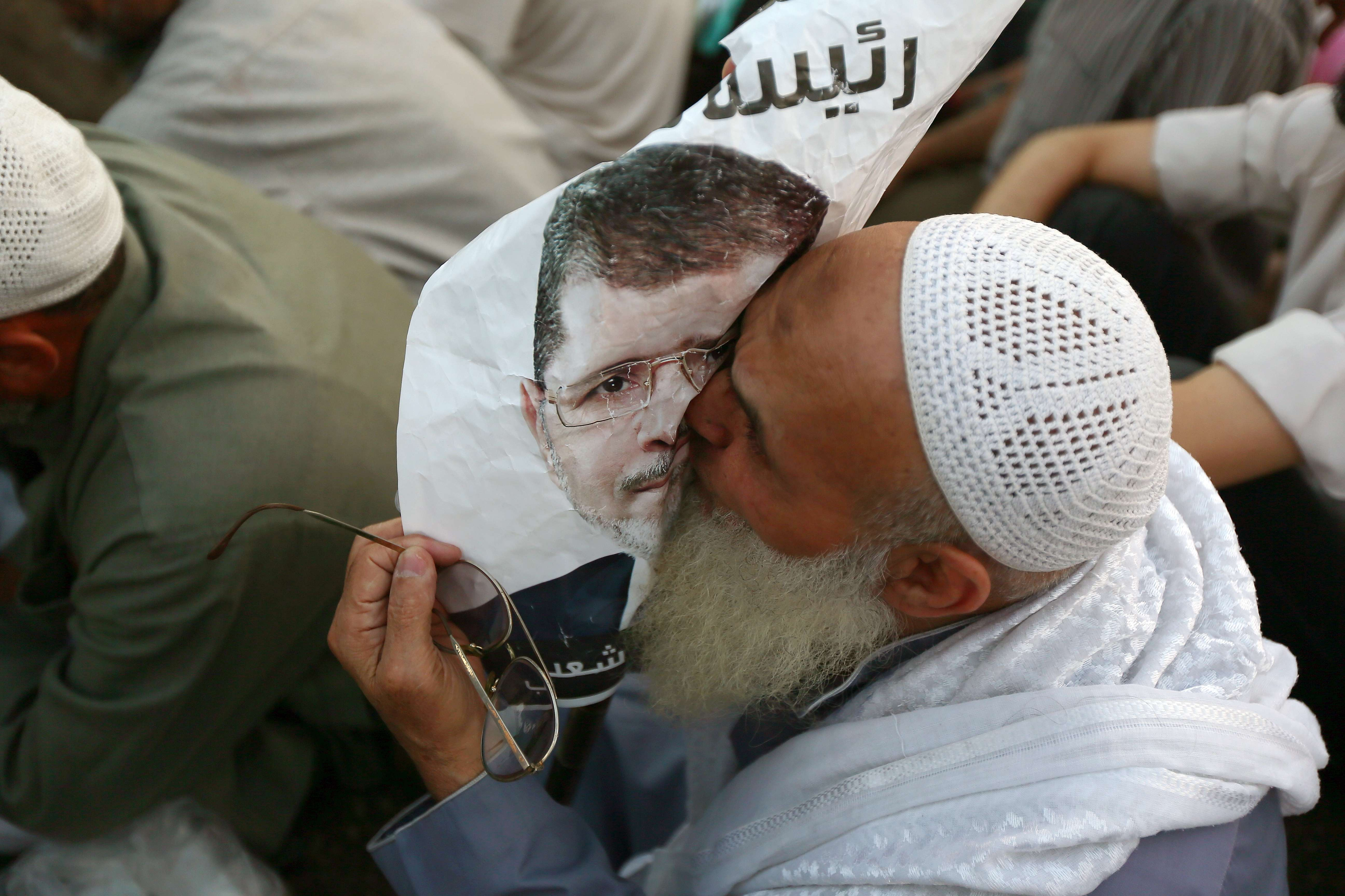 An Egyptian man, supporter of the Muslim Brotherhood and Egypt's ousted president Mohamed Morsi kisses a poster of him as worshipers gather for a dusk payer outside Cairo's Rabaa al-Adawiya mosque on July 11, 2013, during the second day of Islam's holy fasting month of Ramadan. (AFP Photo)
