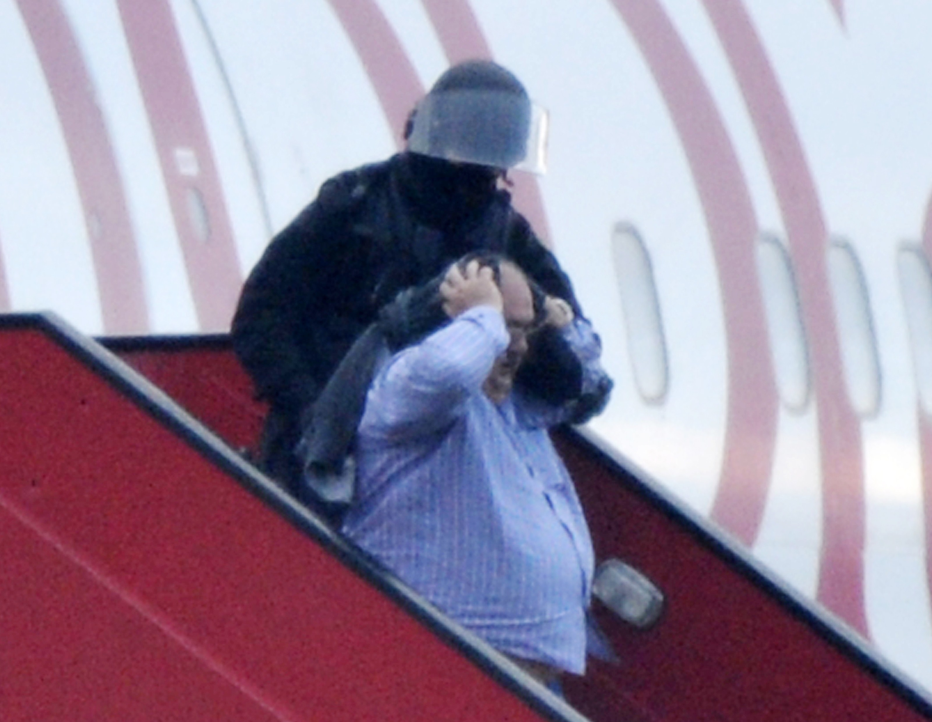 """Police evacuate passengers on February 17, 2014 from the Ethiopian Airlines flight en route to Rome, which was hijacked and forced to land in Geneva, where the hijacker has been arrested, police said. There were no immediate reports of injuries and in a statement in Addis Ababa Ethiopian Airlines said """"the passengers are safe and sound."""" The hijacker was the co-pilot, according to the Geneva airport where the plane was forced to land.  (AFP PHOTO / Richard Juilliart)"""