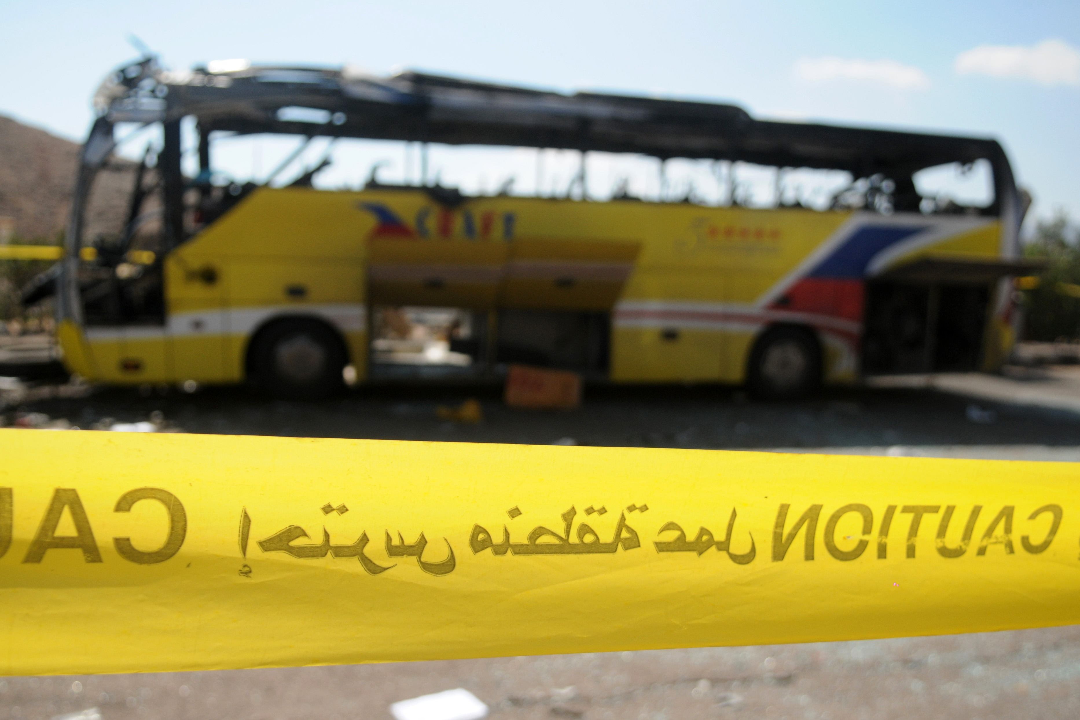 A yellow police tape circles the wreckage of a bus that was targeted the day before by a bomb in the Egyptian south Sinai resort town of Taba on February 17, 2014. Egyptian police said they believe a suicide bomber triggered the blast in a bus that killed three South Korean tourists and the Egyptian driver.  (AFP PHOTO/NAMEER GALAL)