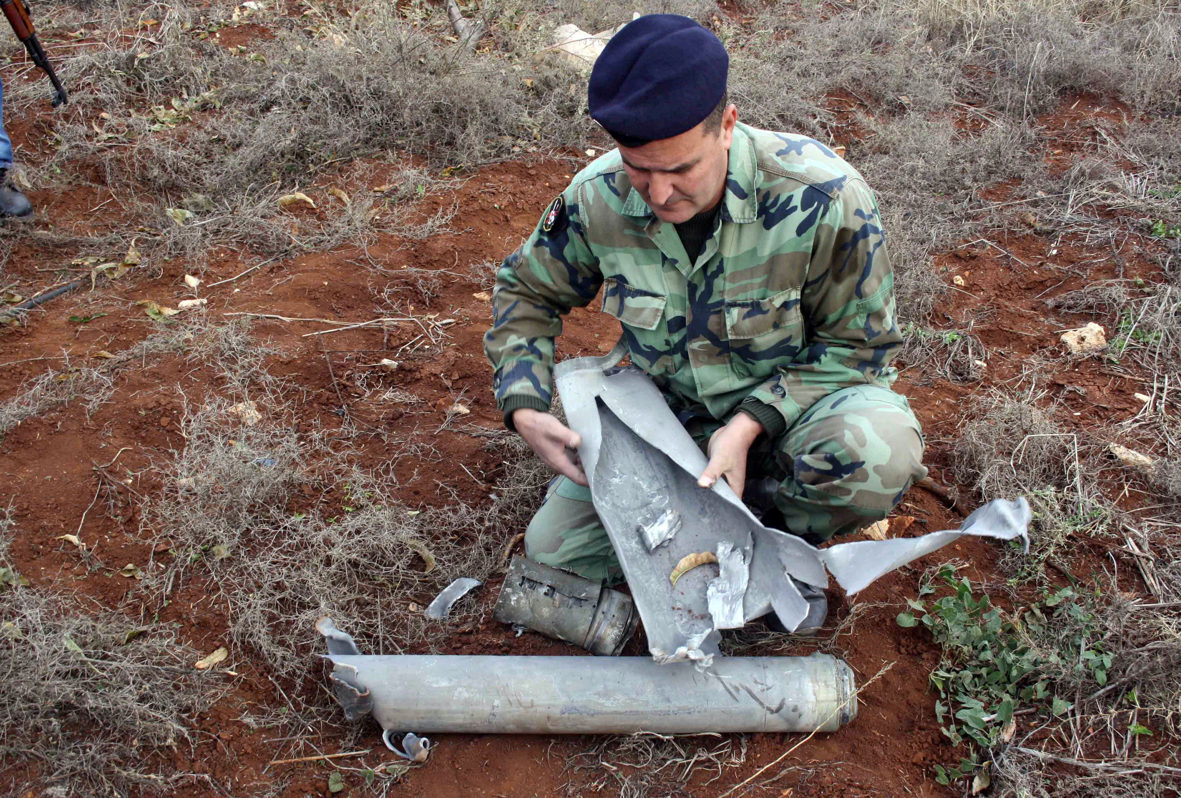 A Lebanese soldier examines of one 20 the shells that were fired by the Israeli army into southern Lebanon on December 29, 2013, without causing any damage. The barrage came after the Israeli military said it had responded to rockets that reportedly struck an open field west of the town of Kyriat Shmona without causing any casualties or damage.  (AFP PHOTO/ALI DIA)