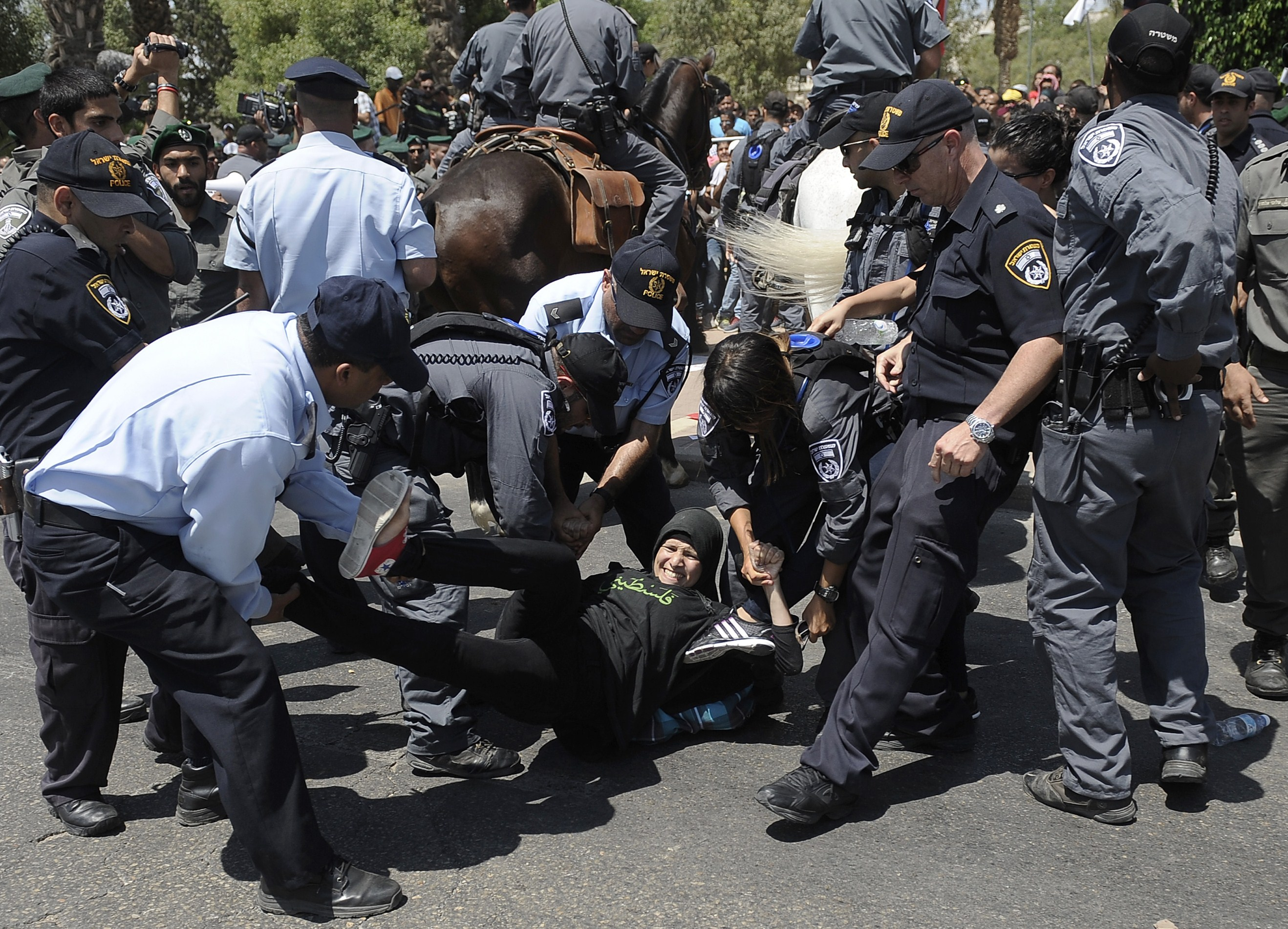 A Bedouin protestor (C) is detained by Israeli policemen during a demonstration against Israeli government's plans to relocate Bedouins in the Negev desert, on July 15, 2013 in the southern city of Beersheva. (AFP Photo)