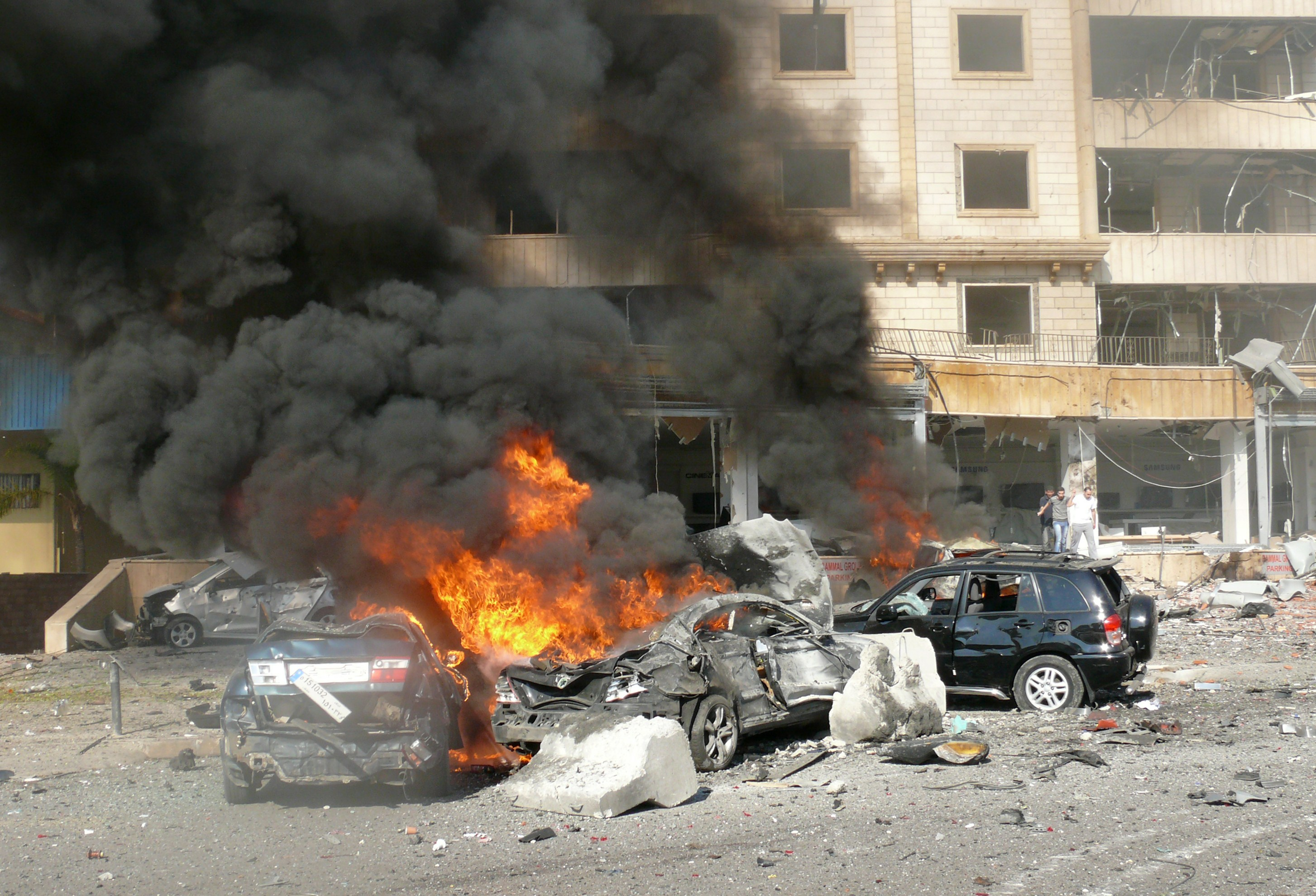 Flames rise from the wreckage of cars following a bomb explosion in a outhern suburb of the capital Beirut on February 19, 2014. Twin bomb blasts appeared to target the Iranian cultural centre, and an AFP photographer at the scene said the blasts had occurred beyond a security checkpoint at the centre, close to the building.  (AFP PHOTO / STR)