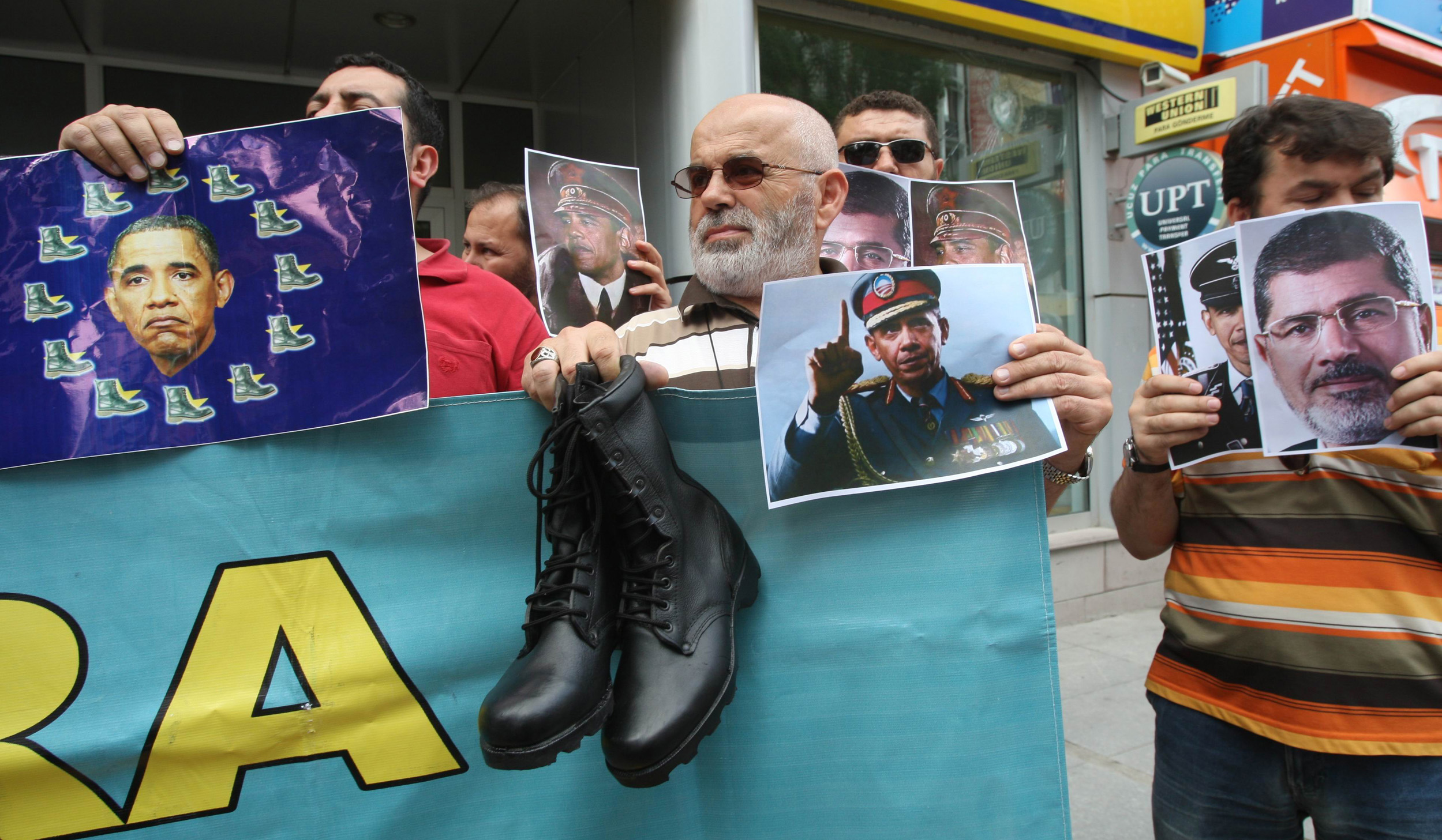 Turkish pro-Islamists demonstrate with military boots they plan to send to the US President Barack Obama (on poster at center) and to the European Union in protest for their alleged supports to the ousting of Egyptian President Mohammed Morsi (on poster at right) in Ankara, on July 17, 2013.  (AFP PHOTO / ADEM ALTAN)