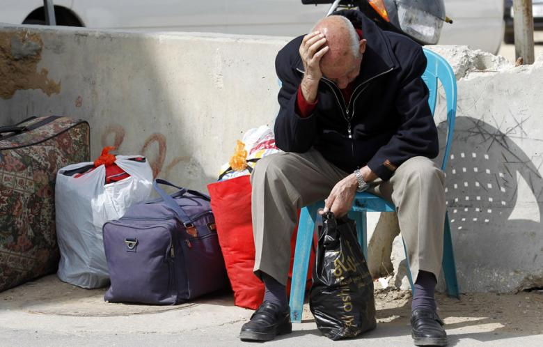 A Palestinian man waits with his stuff near the gate of the Rafah border crossing on February 2014.  (AFP Photo/ Said Khatib)