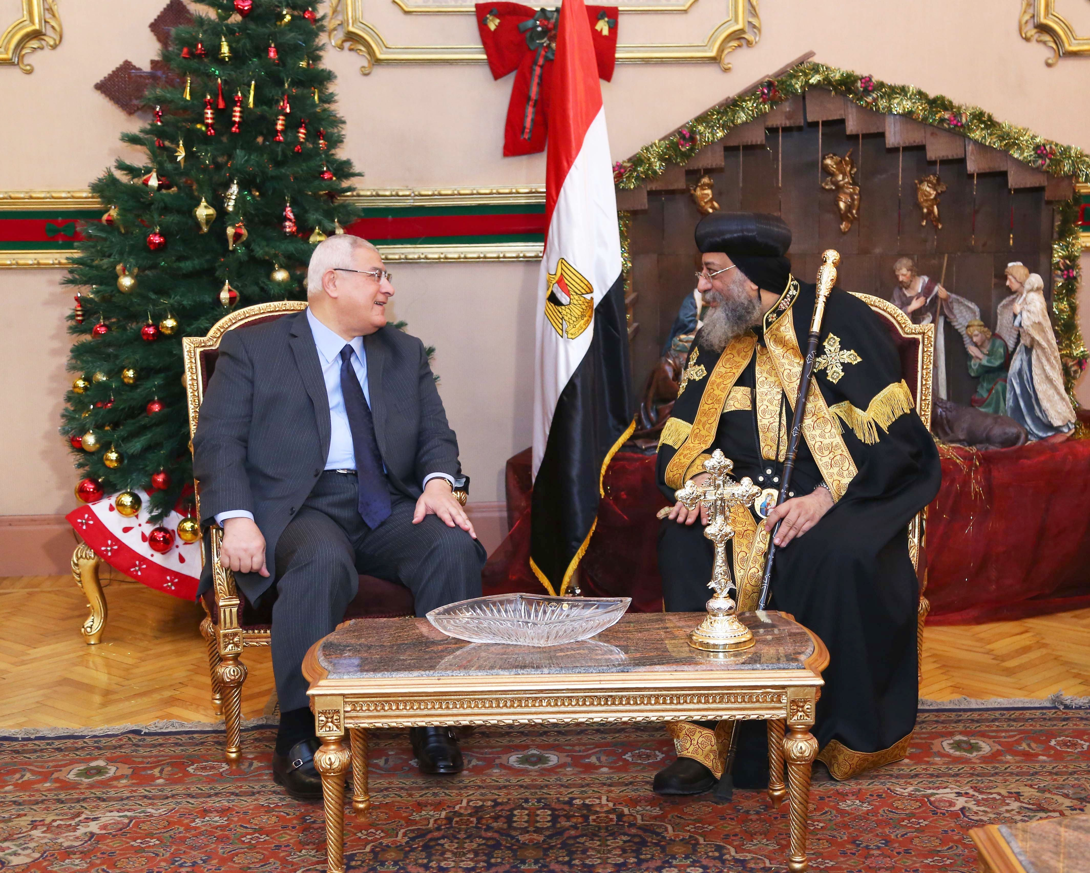 """A handout picture released by Egyptian Presidency shows interim President Adli Mansour (L) wishing the leader of the Egyptian Coptic Orthodox Church, Pope Tawadros II, a happy Christmas at the Saint Mark's Coptic headquarters in Cairo's Abbassiya neighbourhood, during his visit on January 5, 2014, as the Coptic church celebrates Orthodox Christmas.  AFP PHOTO / HO / EGYPTIAN PRESIDENCY  === RESTRICTED TO EDITORIAL USE - MANDATORY CREDIT """"AFP PHOTO/HO/EGYPTIAN PRESIDENCY"""" - NO MARKETING NO ADVERTISING CAMPAIGNS - DISTRIBUTED AS A SERVICE TO CLIENTS ==="""