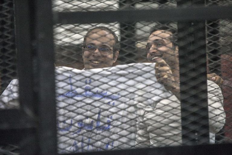 Egyptian activists Ahmed Maher (L) and Ahmed Douma hold up a T-shirt reading Drop the law on demonstrations during their trial in Cairo over an unlicensed protest on 8 December 2013 (AFP File Photo/ Mahmoud Khaled )