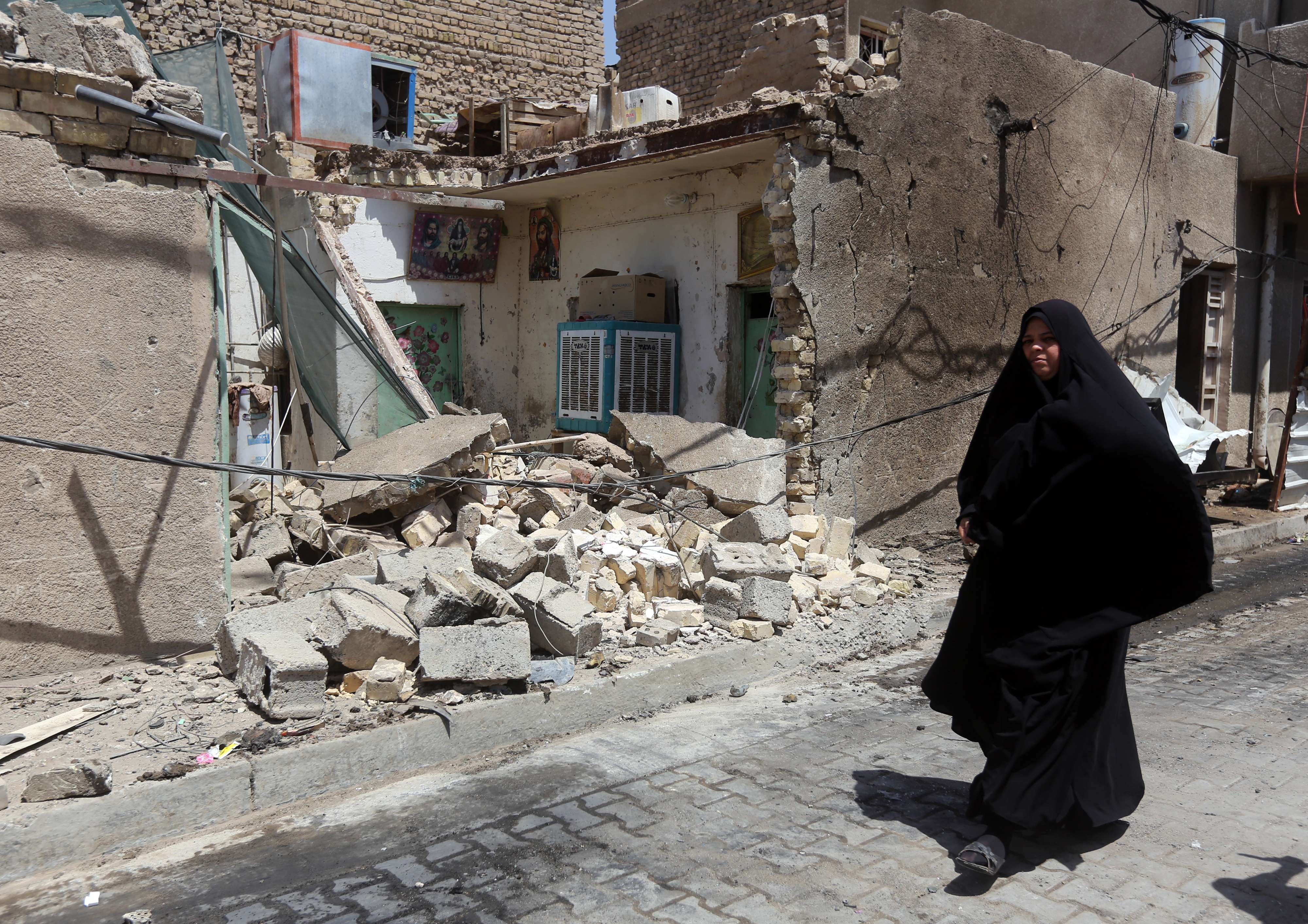An Iraqi woman walks past a house damaged by a car explosion on Tuesday  in Baghdad's northern Shiite-majority district of Sadr City. A spate of rush hour car bombs rocked Shiite-majority areas of Baghdad, killing 25 people in the first major series of attacks to hit the Iraqi capital since elections last month. (AFP PHOTO / AHMAD AL-RUBAYE)