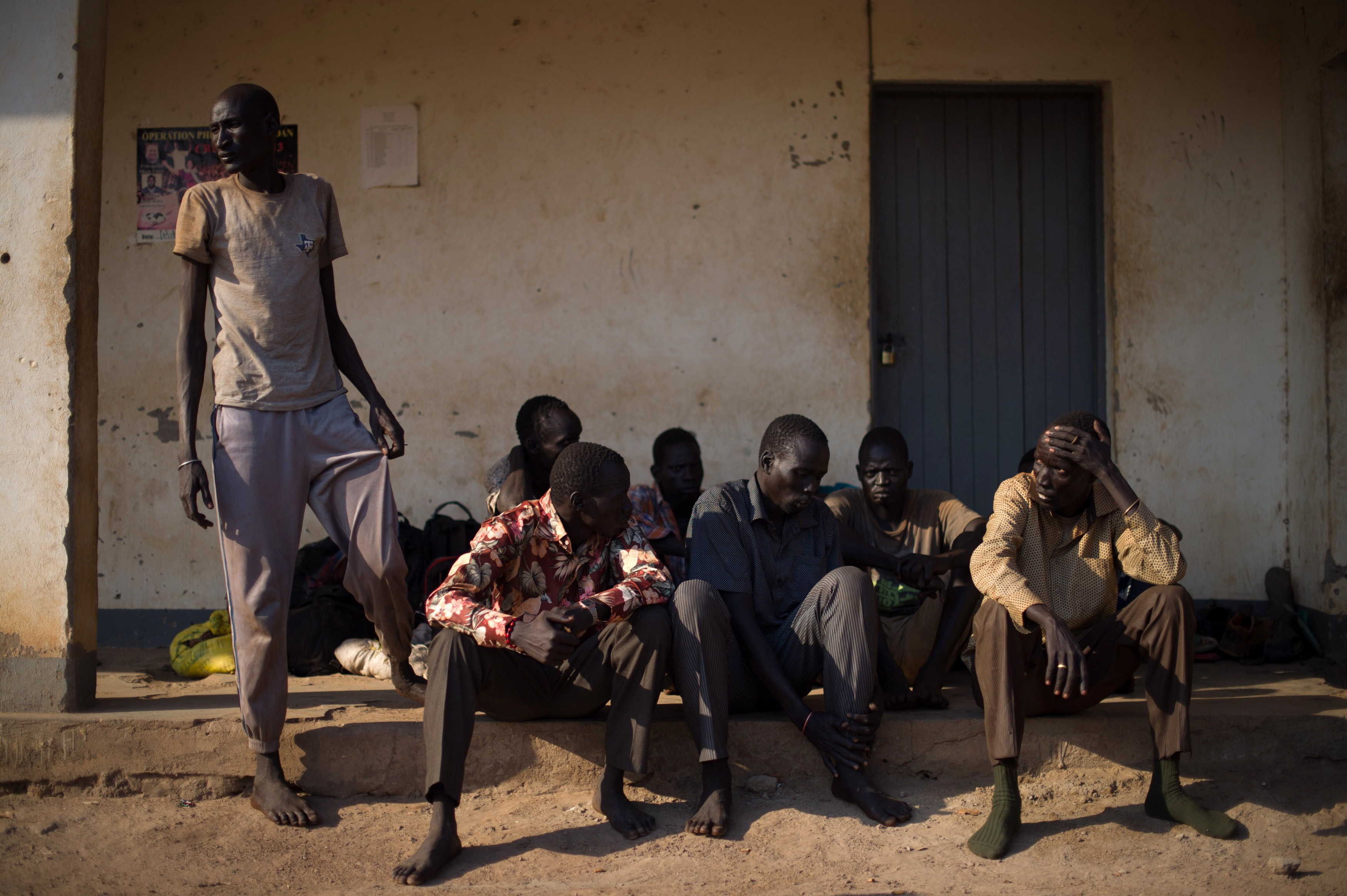 Men who claim to have deserted theSudan People's Liberation Army (SPLA) sit outside a police station in Mvolo, about 120 kms (75 miles) from Rumbek in the Western Equatoria State, on Tuesday (AFP PHOTO/PHIL MOORE)