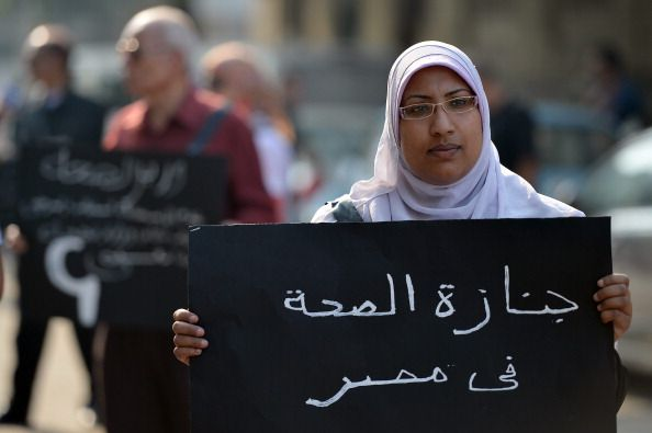 "An Egyptian doctor who is on strike carries a placard that reads ""The funeral of Egypt's health"" during a march in central Cairo on 8 November, 2012.  (Khaled Desouki/AFP/Getty Images)"