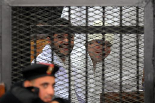 Egyptian activicts Ahmed Douma (left) and Ahmed Maher, the founder of the April 6 youth movement that led the revolt against Hosni Mubarak, stand in the dock during their trial on 22 December  (AFP File Photo)