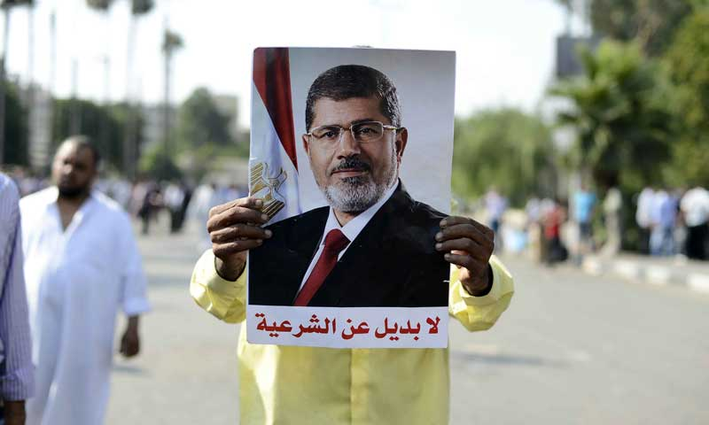 "A pro-Morsi protester holds a poster of the ousted president which reads ""There's no alternative to legitimacy"" (AFP/ file photo)"