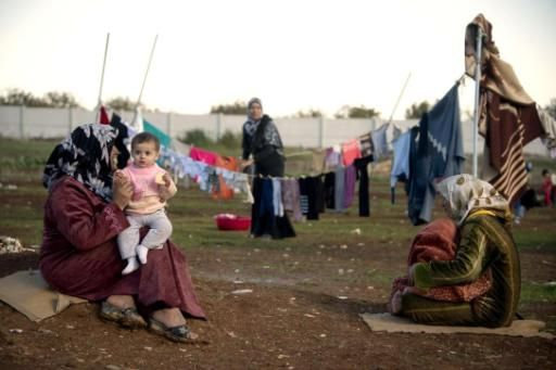 Mothers and their children sit among their washing in a refugee camp on the border between Syria and Turkey near the northern city of Azaz  ( AFP File Photo / Odd Andersen )
