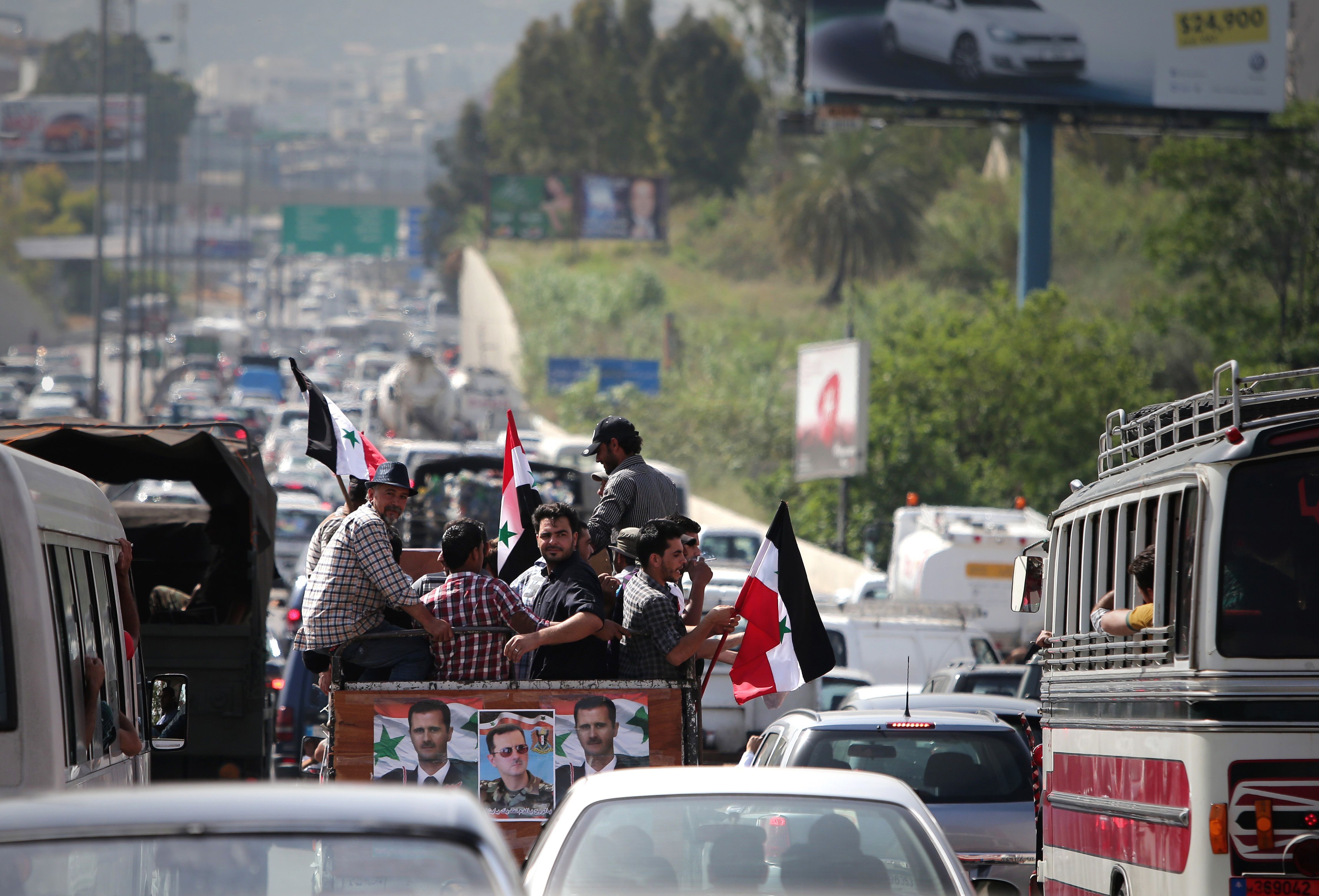 Syrian expatriate living in Lebanon ride in a truck with posters of Syrian president Bashar al-Assad as they drive to the Syrian Embassy in Yarze east of Beirut on May 28, 2014, to vote in the country's presidential elections.  (AFP PHOTO/ JOSEPH EID)