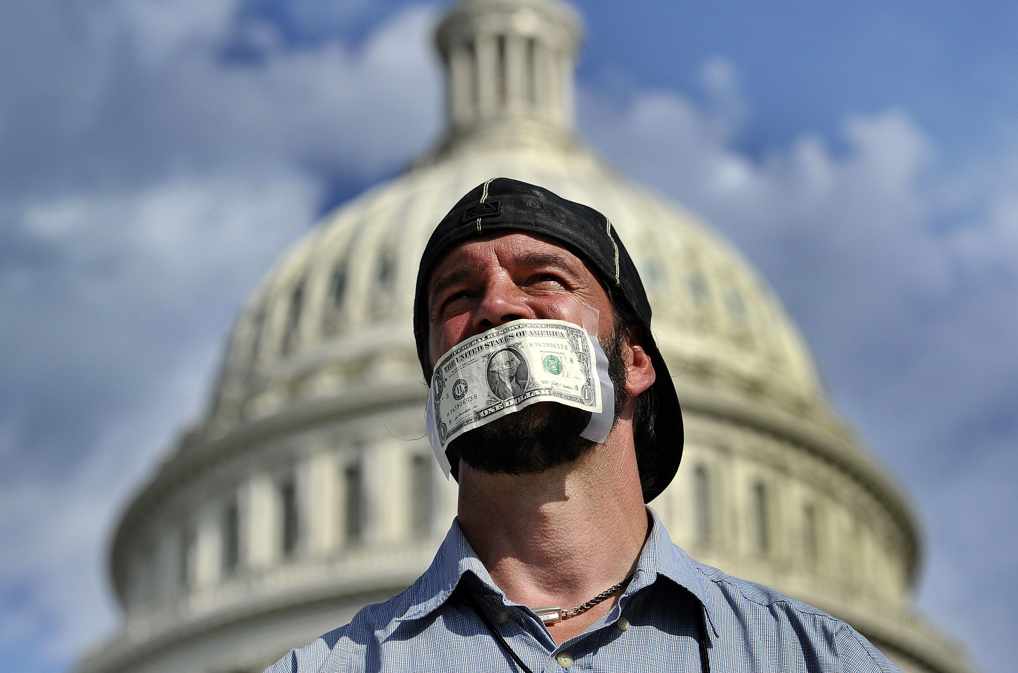 Protester covers his mouth with a dollar bill as he joins others in a demonstration in front of the US Capitol in Washington, DC, on Tuesday urging congress to pass the budget  (AFP Photo / Jewel Samad)