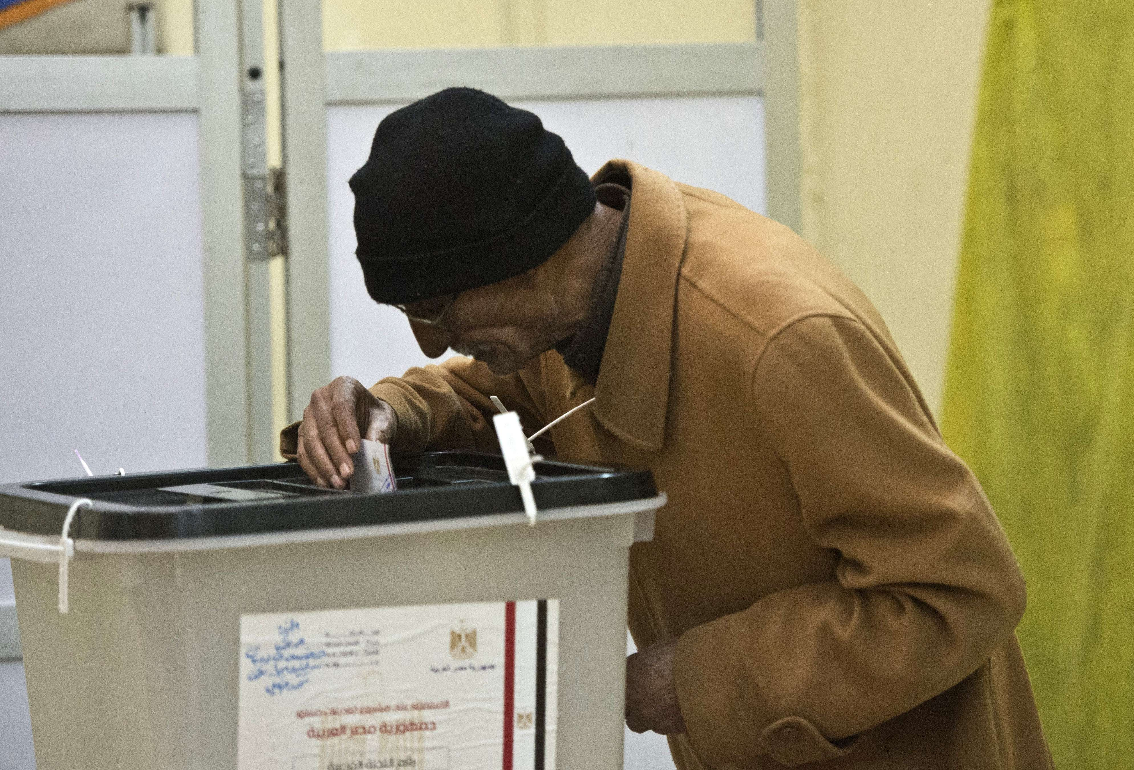 An Egyptian man casts his ballot as he votes on a new constitution on January 14, 2014 at a polling centre  in Cairo. Egyptians vote on a new constitution amid high security in a referendum likely to prompt a presidential bid by the army chief who overthrew Islamist president Mohamed Morsi.     (AFP PHOTO / KHALED DESOUKI)