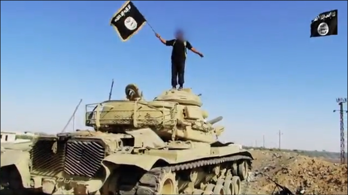 A 'State of Sinai' militant standing atop a tank at the site of the 24 October attack that killed at least 30 military personnel  (Screenshot from 'State of Sinai' video)
