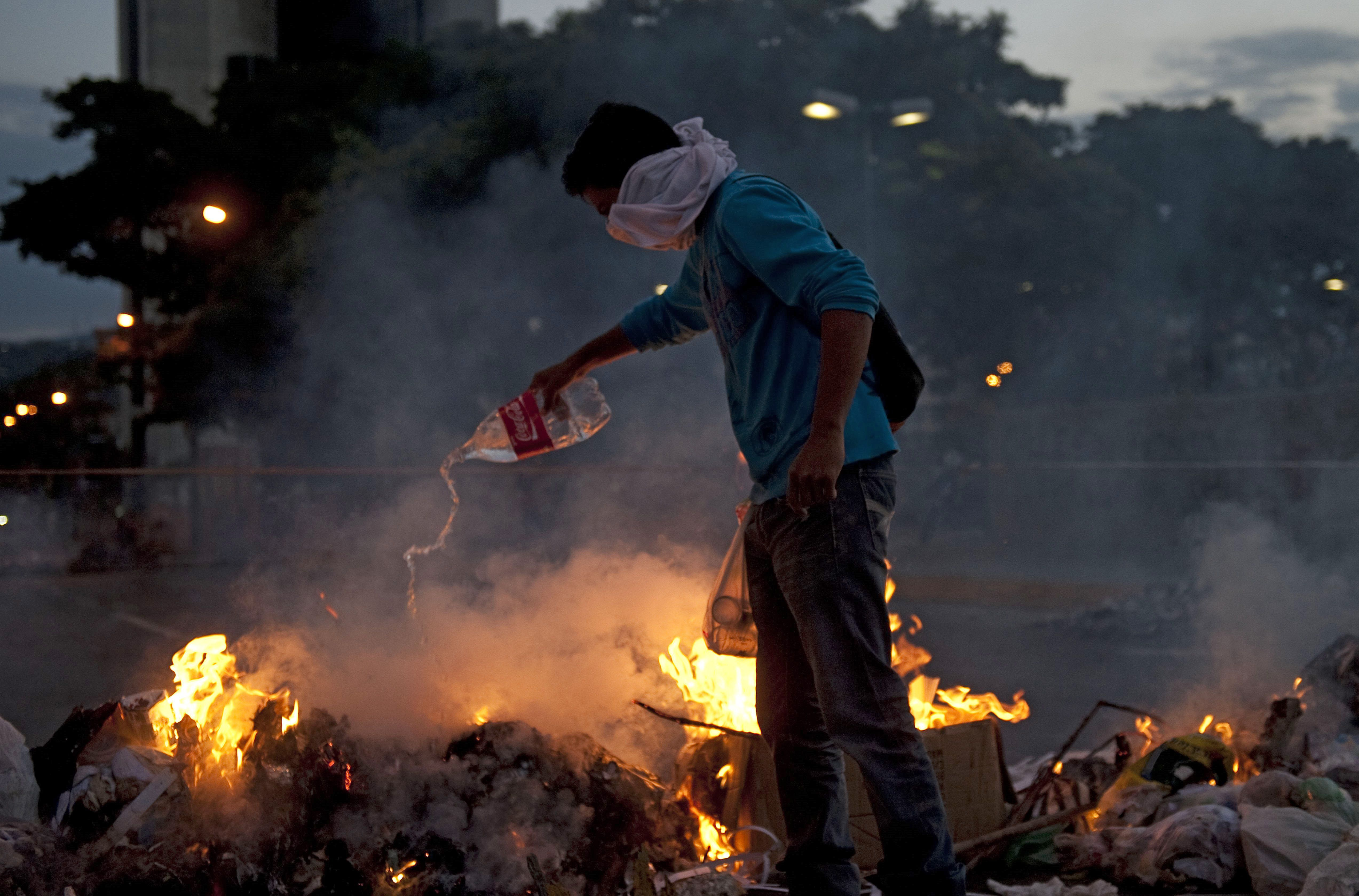 A Venezuelan anti-government student lights a fire during clashes with riot policemen following a protest, in Caracas on February 20, 2014. Venezuelan President Nicolas Maduro, successor of the late Hugo Chavez, is under fire over what protesters say is rampant crime, runaway inflation, high unemployment and other economic problems.   (AFP PHOTO / Raul ARBOLEDA)
