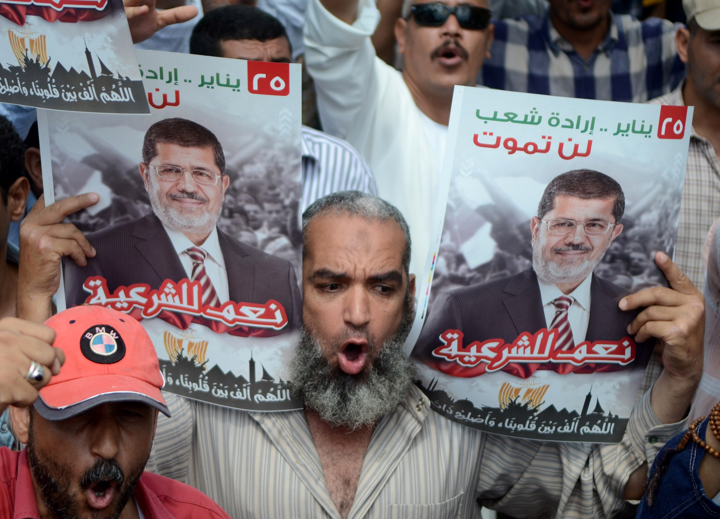 A supporter of the Muslim Brotherhood and Egypt's ousted president Mohamed Morsi (portrait) holds pictures of the former Islamist leader and shout slogans during a demonstration in the coastal city of Alexandria on July 19, 2013. (AFP Photo)
