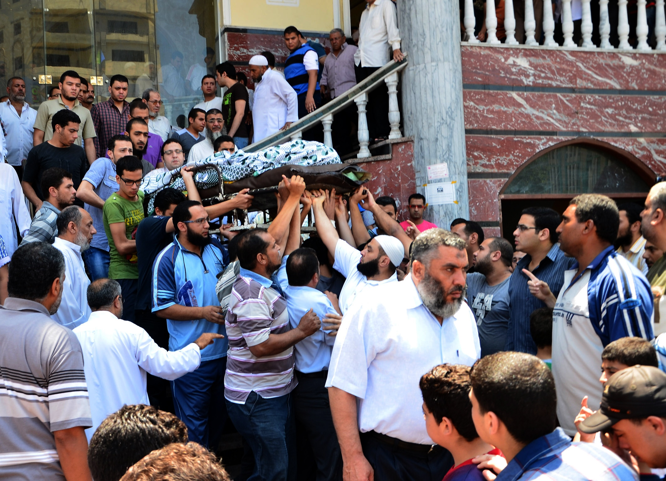 Egyptian people carry the body of a victim of the clashes that broke out between supporters and opponents of Egypt's depose president Mohamed Morsi during a funeral ceremony on July 20, 2013 in the Nile delta city of Mansura. (AFP Photo)