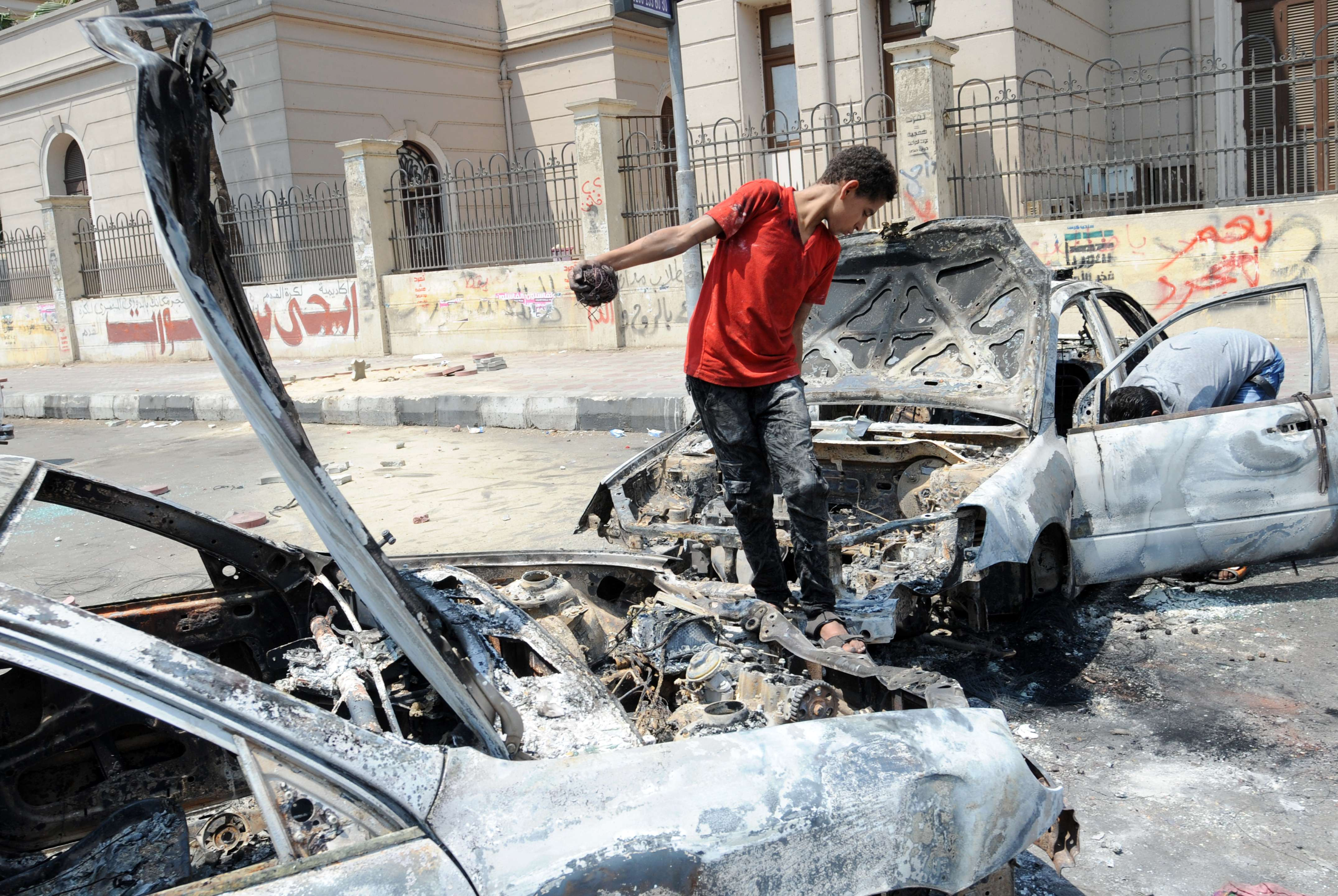 An Egyption youth inspects a burnt car near Cairo University on July 23, 2013, where supporters of Egypt's deposed president Mohamed Mursi are holding an open sit in. (AFP Photo)