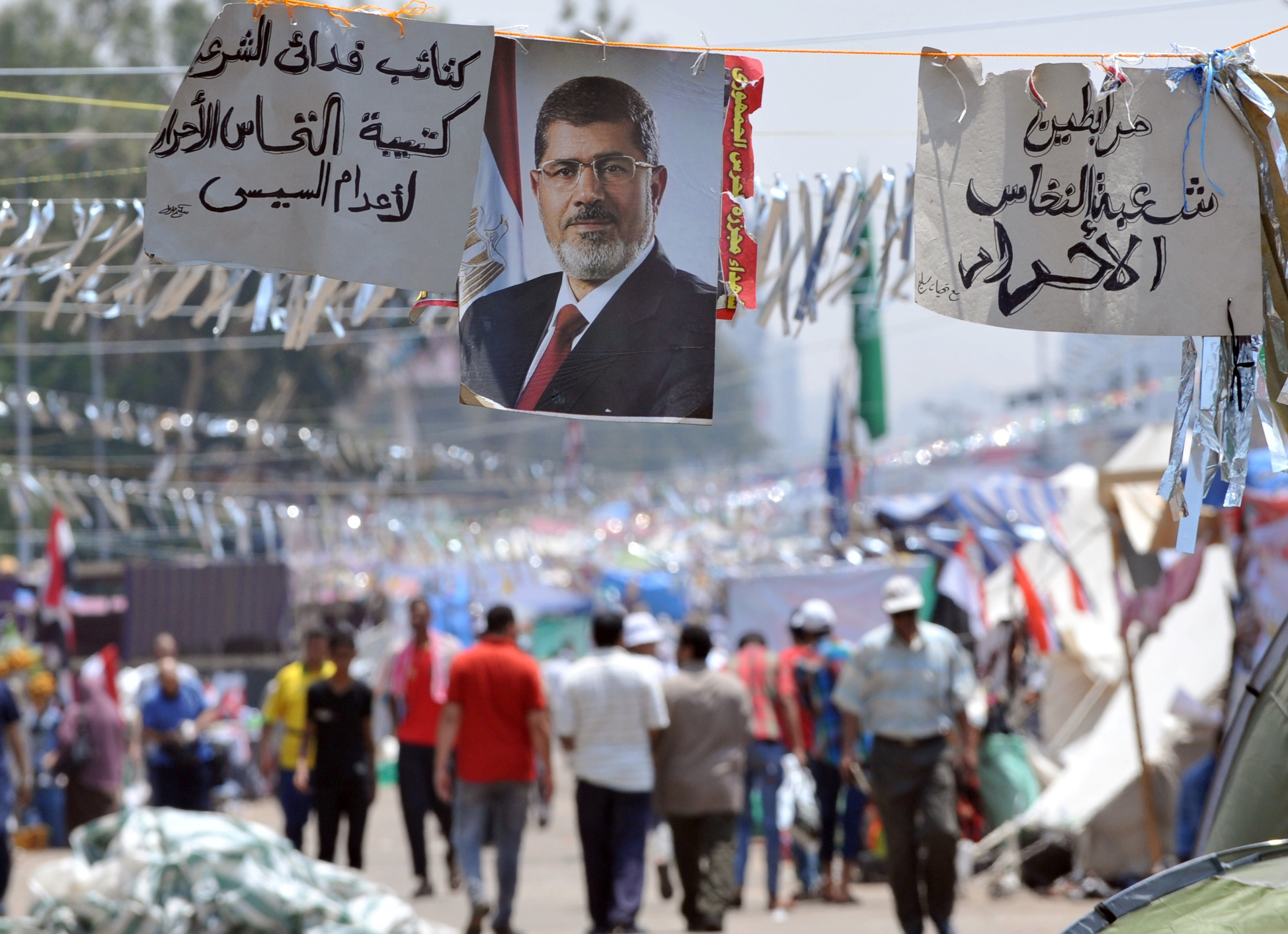 Supporters of Egypt's deposed president Mohamed Morsi walk past his portrait in Cairo on July 23, 2013 during a sit in outside Rabaa al-Adawiya mosque.  (AFP Photo)