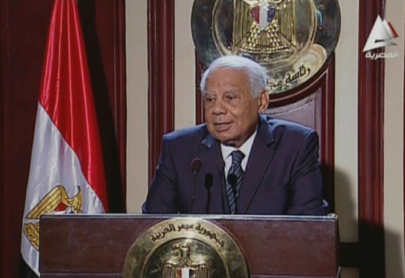 "An image grab taken from Egyptian state TV shows Egypt's Premier Hazem al-Beblawi addressing the media in Cairo on February 24, 2014 as his government submitted its resignation to interim president Adly Mansour in a move just weeks before a presidential poll.  AFP PHOTO / EGYPTIAN TV  == RESTRICTED TO EDITORIAL USE - MANDATORY CREDIT ""AFP PHOTO / EGYPTIAN TV"" - NO MARKETING NO ADVERTISING CAMPAIGNS - DISTRIBUTED AS A SERVICE TO CLIENTS ==="