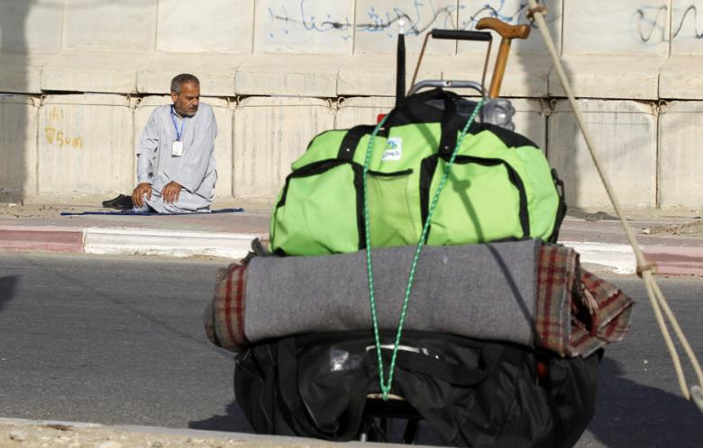 A Palestinian Muslim pilgrim prays at the Rafah border crossing with Egypt as he waits to cross the frontier to continue his journey to the Muslim holy city of Mecca for the annual Hajj pilgrimage on 2 October 2013.  ( AFP Photo \ Said Khatib)