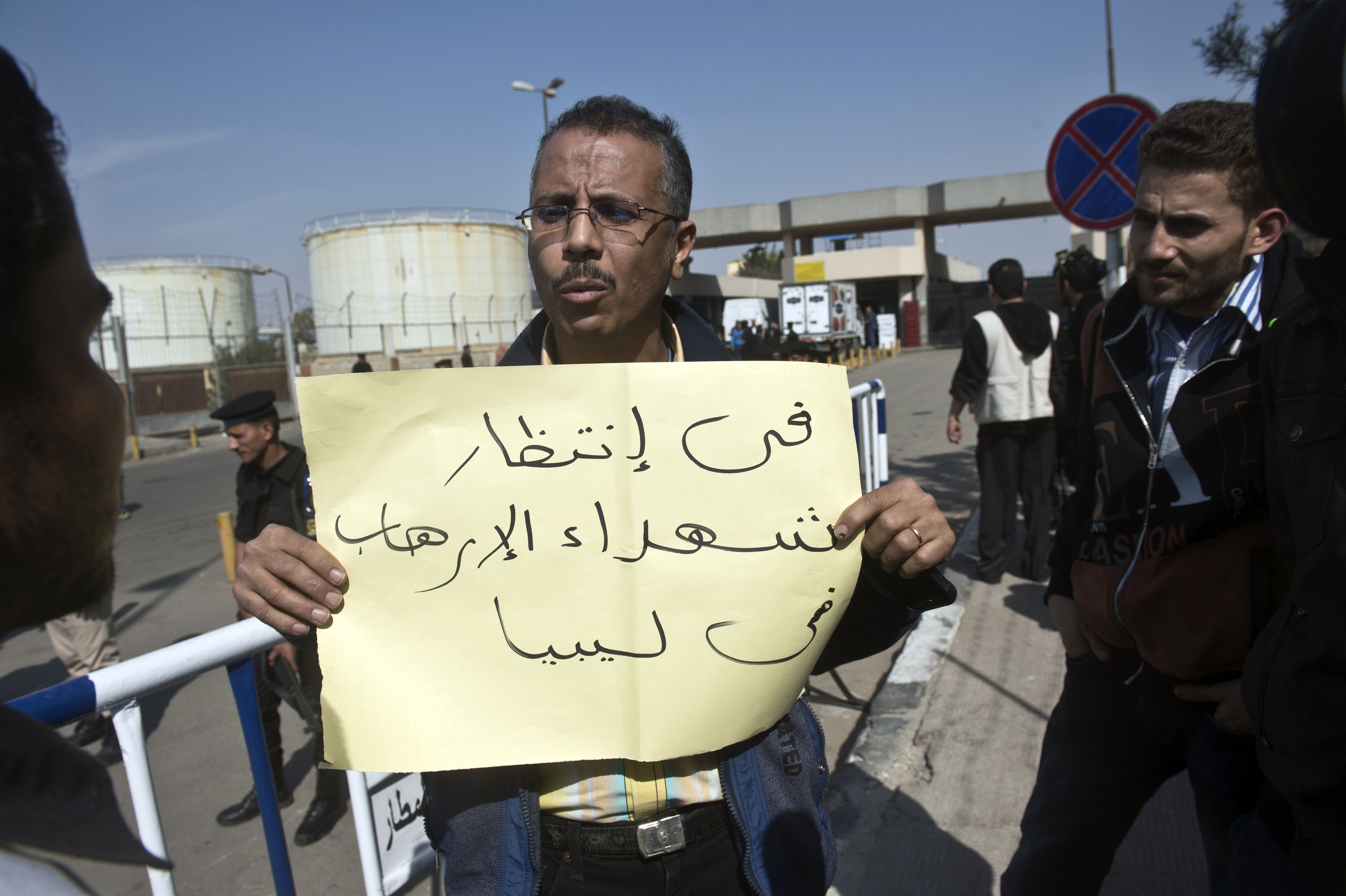 """An Egyptian man holds a sign reading in Arabic: """"waiting for martyrs of terrorism in Libya"""" as ambulances drive out of Cairo international airport on February 26, 2014, carrying the bodies of seven Egyptian victims who were found shot dead  in Jalluta, near Benghazi in eastern Libya, the previous day.  The victims were kidnapped from their home late on February 23, by an unknown group, an Egyptian foreign ministry spokesman said, adding that eight men had been taken originally but one escaped by throwing himself from his abductors' car. (AFP PHOTO / KHALED DESOUKI)"""