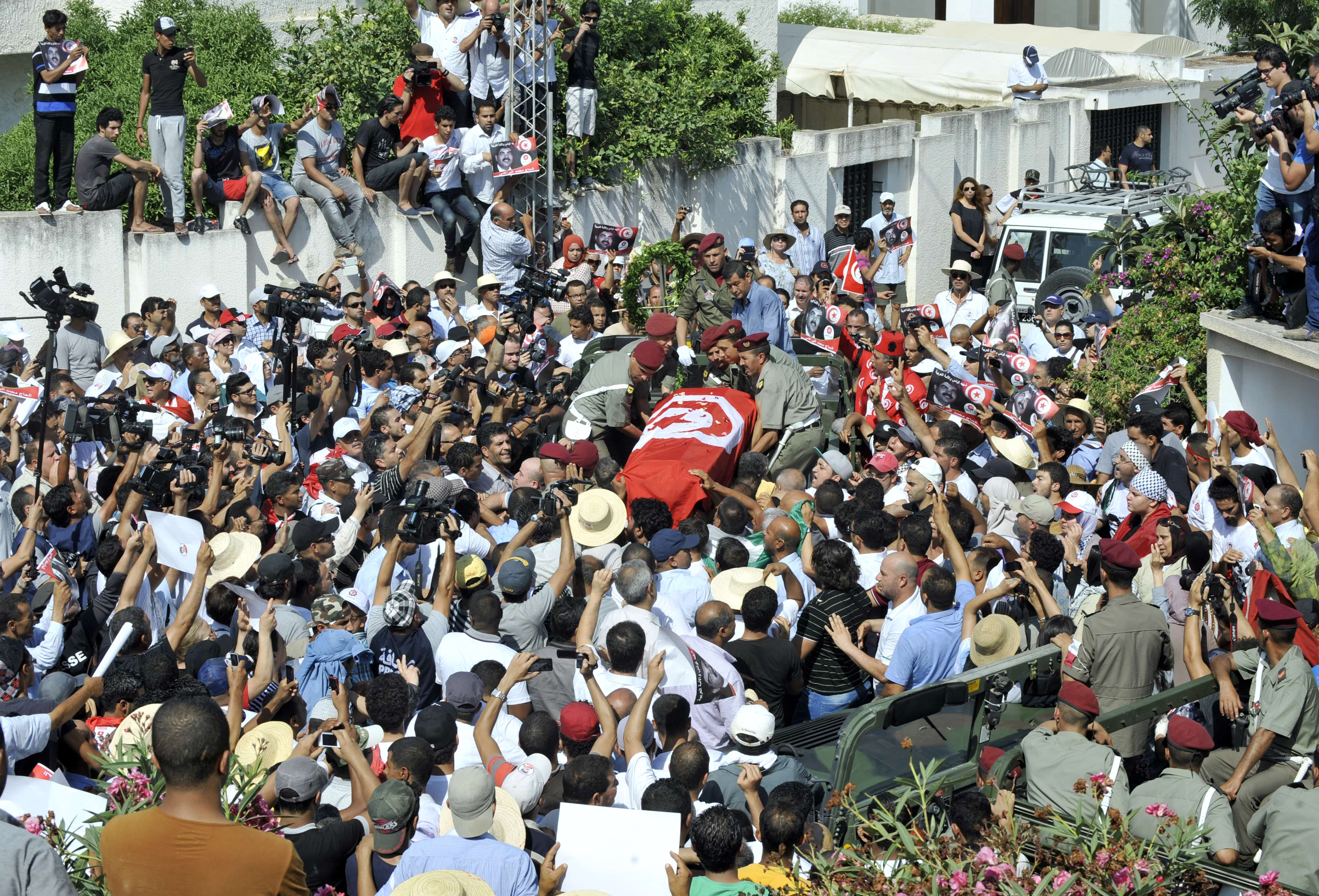 Tunisian soldiers load the coffin of assassinated opposition leader Mohamed Brahmi as his funeral procession takes place under military escort on July 27, 2013 in Tunis. (AFP Photo)