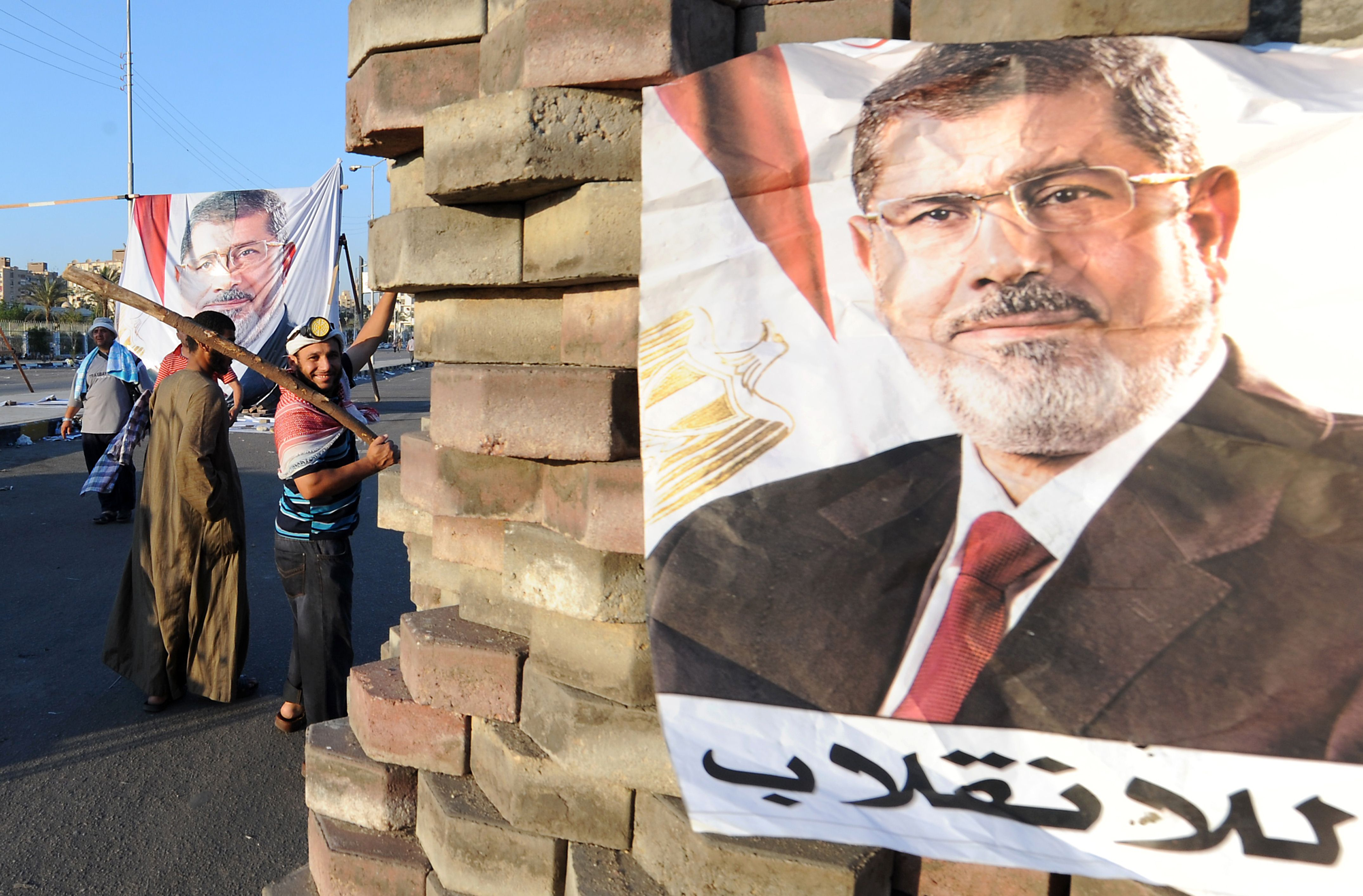 Supporters of the Muslim Brotherhood gestures as they stand close to an image of deposed president Mohamed Morsi at a makeshift brick barricade erected along Nasr City's main street, a district of eastern Cairo, on July 28, 2013, as supporters of Morsi continue to hold a sit in outside Rabaa al-Adawiya mosque demanding his reinstatement.  (AFP PHOTO/FAYEZ NURELDINE)