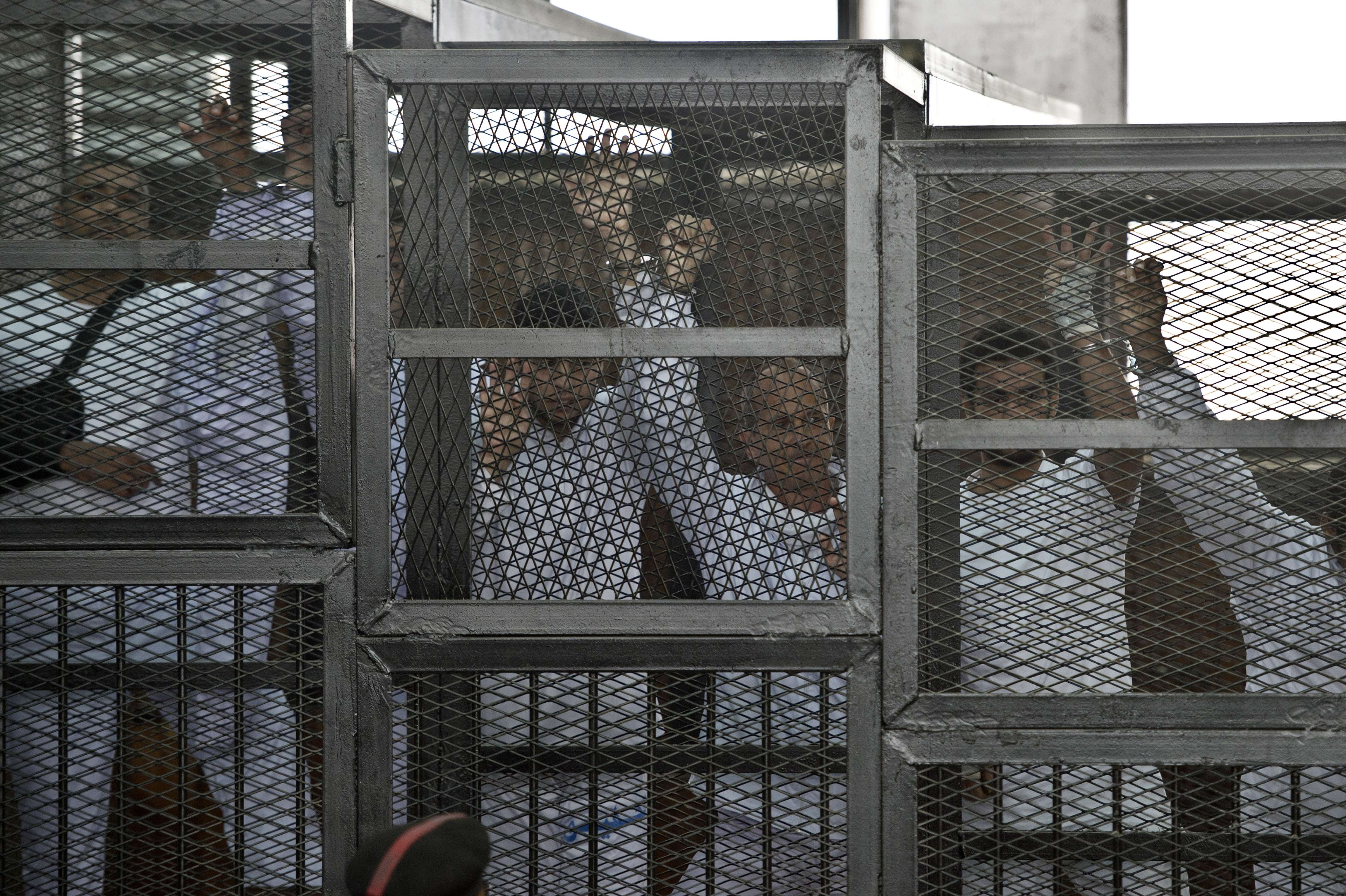 Australian journalist Peter Greste (C) of Al-Jazeera and his colleagues stand inside the defendants cage during their trial for allegedly supporting the Muslim Brotherhood at Cairo's Tora prison on March 5, 2014.  (AFP PHOTO / KHALED DESOUKI)