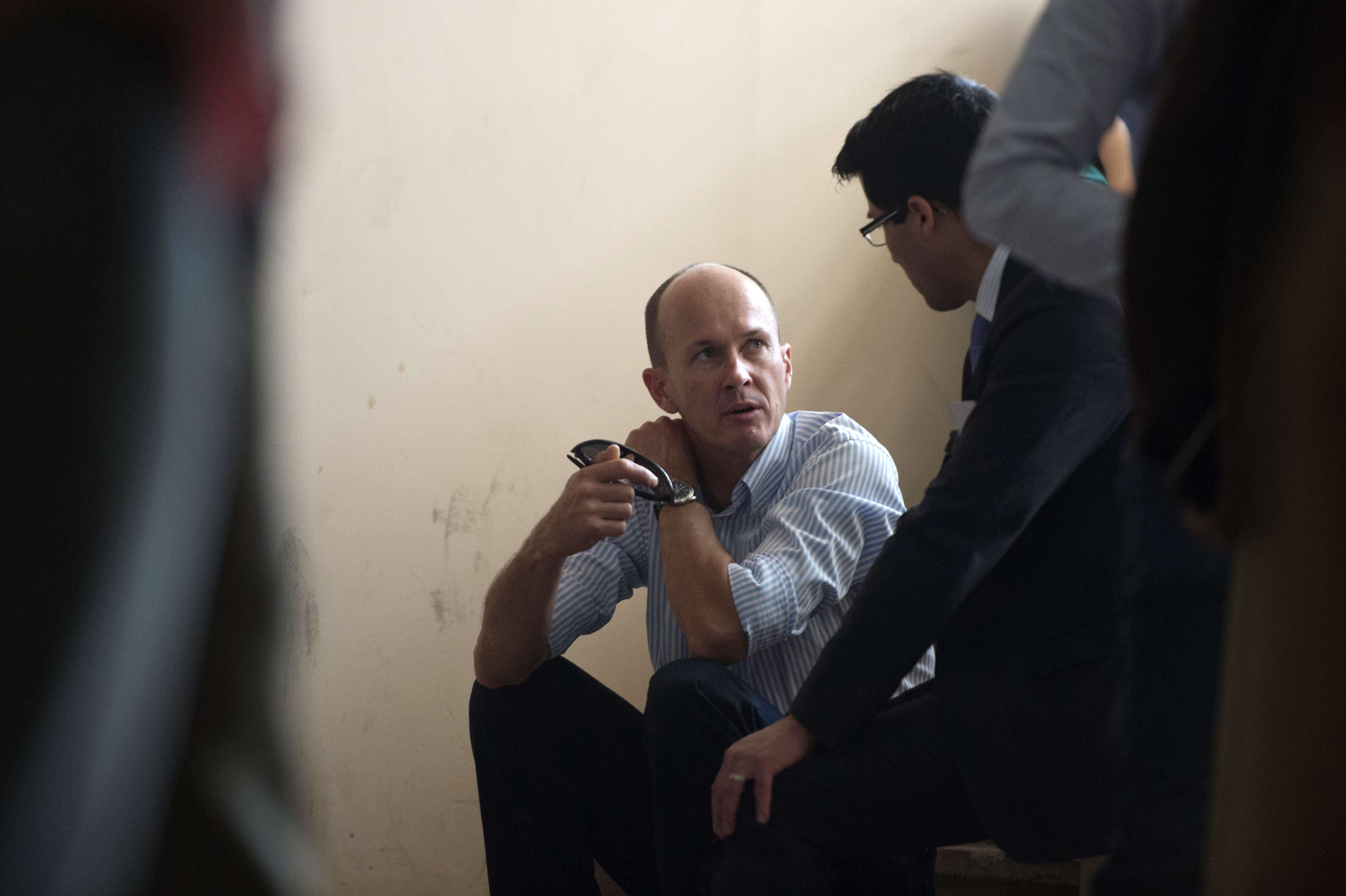Andrew Greste, brother of the Australian journalist Peter Greste of Al-Jazeera, talks sitting on stairs during the trial of his brother along with his colleagues for allegedly supporting the Muslim Brotherhood at Cairo's Tora prison on March 5, 2014. The high-profile case that sparked a global outcry over muzzling of the press is seen as a test of the military-installed government's tolerance of independent media, with activists fearing a return to autocracy three years after the Arab Spring uprising that toppled Hosni Mubarak.   (AFP PHOTO / KHALED DESOUKI)