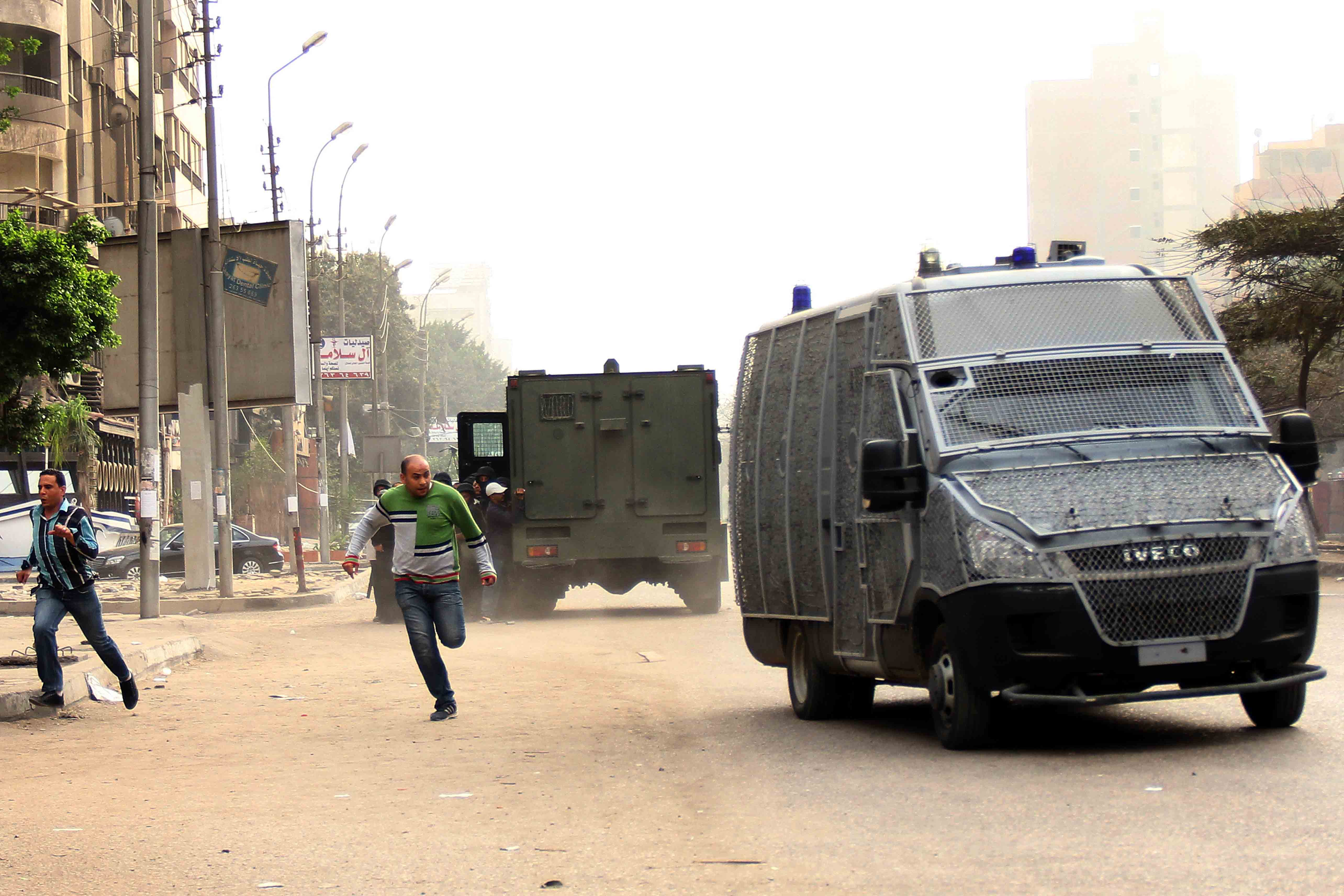 Egyptian protestors run for covers near police vehicles during clashes with Egyptian police following a demonstration in support of the Muslim Brotherhood and Egypt's ousted president Mohamed Morsi in the Ain Shams district of the capital Cairo on March 7, 2014.  (AFP PHOTO / AHMED TARANA)