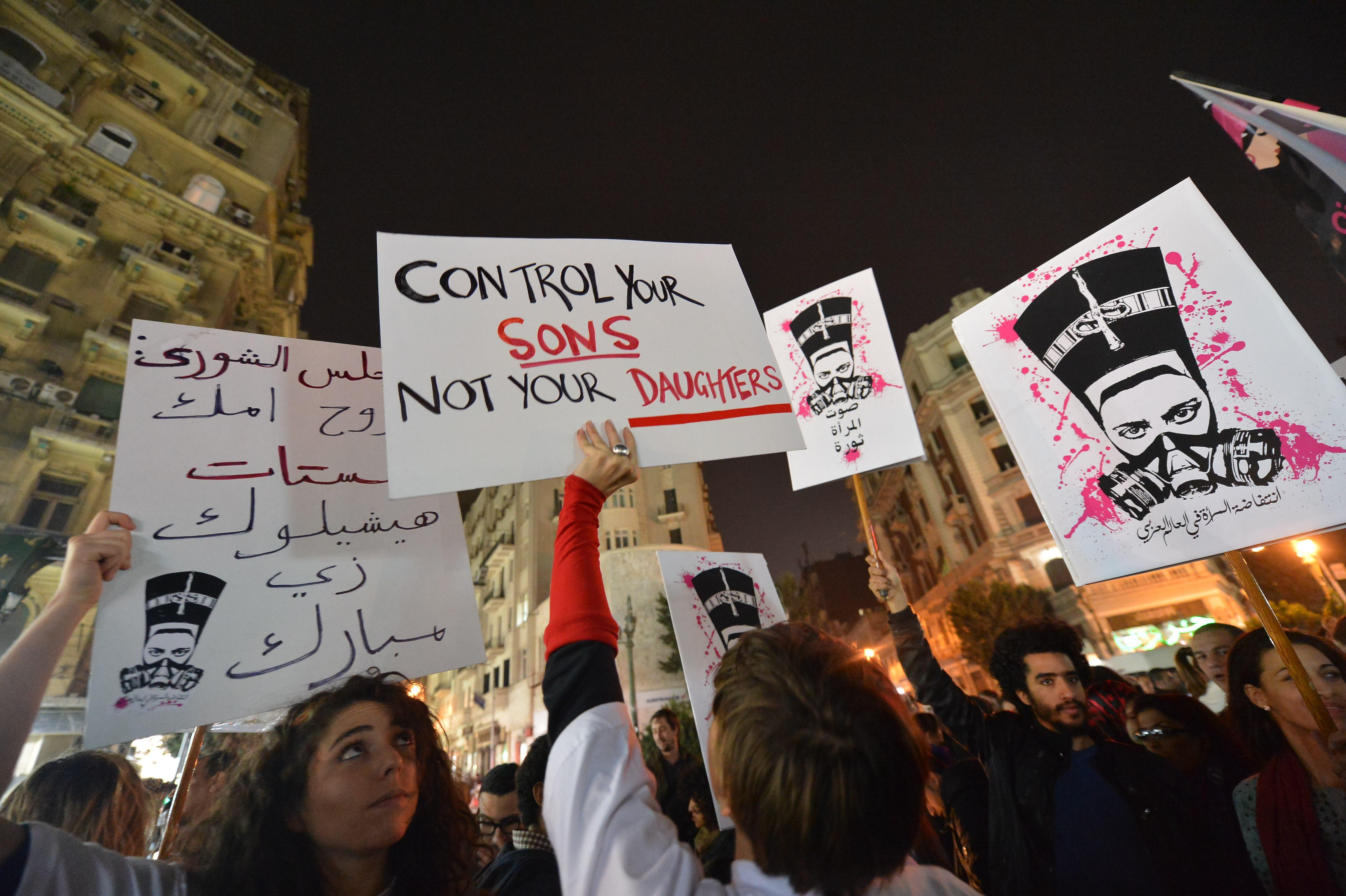Egyptian protesters hold up placards and shout slogans during a demonstration in Cairo against sexual harassment on February 12, 2013.  (AFP Photo)