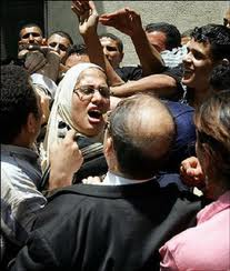 An Egyptian woman screams as she and other members of the left-wing umbrella organization Kefaya (Enough) are roughed-up by supporters of Egyptian President Hosni Mubarak while participating in a protest in Cairo against the referendum on changing the electoral system on 2005. (AFP File Photo /Cris Bouroncle)