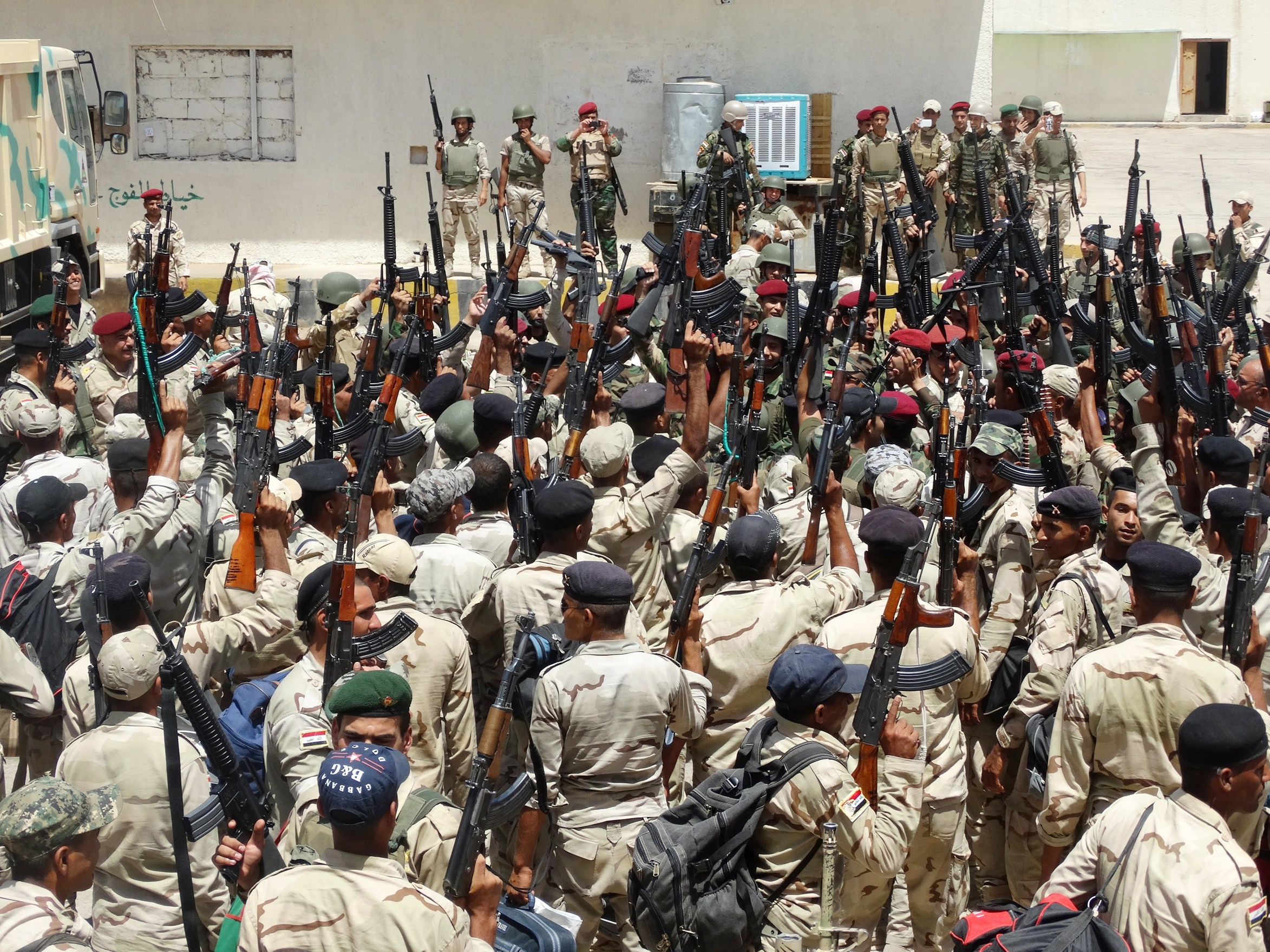 Iraqi troops raise up their weapons as they gather upon their arrival to support the Sunni anti-Al-Qaeda militia Sahwa (Awakening) in its fight against anti-government militants, including from the jihadist Islamic State of Iraq and the Levant (ISIL) in the Anbar province on June 21, 2014 in the city of Ramadi, west of the capital Baghdad.   (AFP PHOTO / STR)