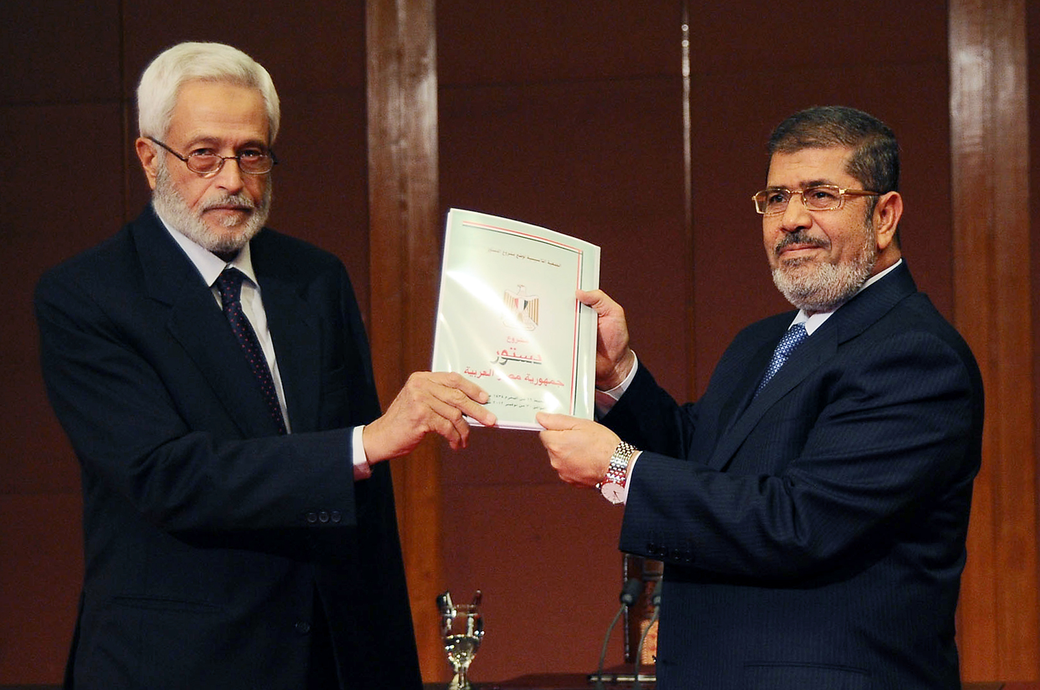 Egypt's president Mohamed Morsi (R) receives a copy of the final draft of Egyptian new constitution from the head of the Islamist-dominated constituent assembly Hossam el-Gheriany, late on December 1, 2012 in Cairo.  (AFP Photo)