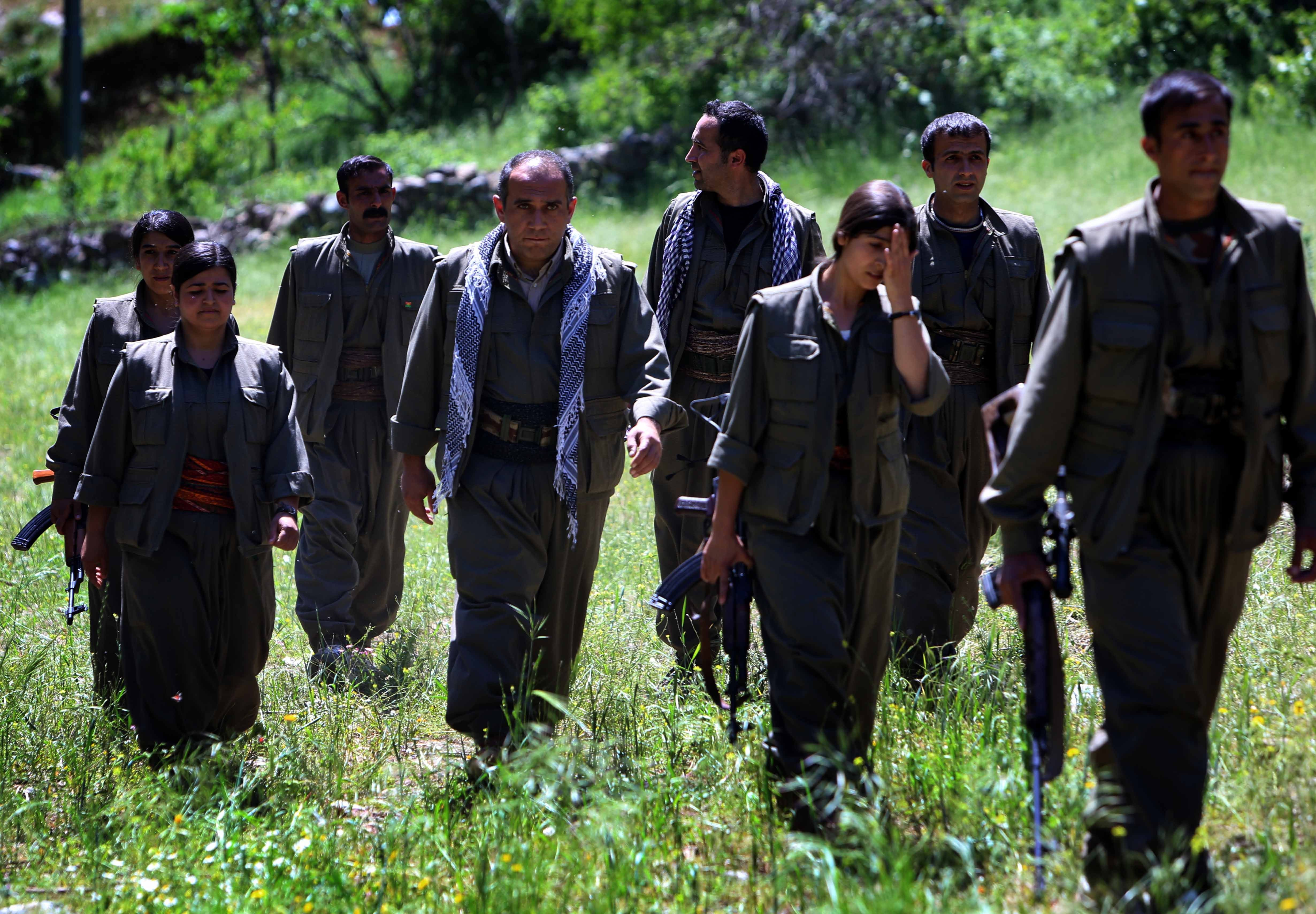 Rezan Javed (4 L), leader of the anti-Iranian group the Kurdistan Free Life Party (PJAK), is surrounded by militants as he makes his way to a press conference in the Qandil mountains of northern Iraq's Kurdish autonomous region, on May 5,2014.  (AFP Photo)