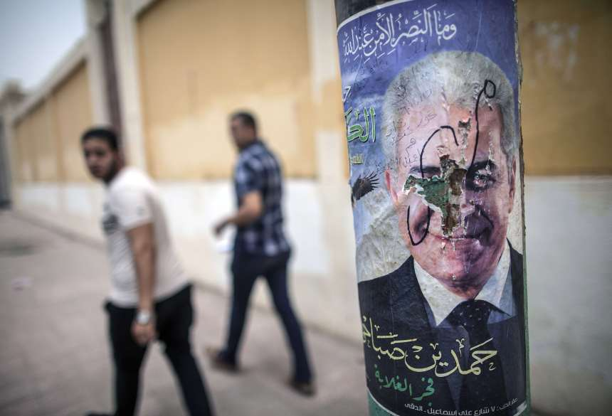 "Egyptian men sit next to defaced campaign poster of Egypt's Hamdeen Sabbahi, the sole rival to the former army chief expected to romp to victory in next week's presidential election, in Fayyum some 100 kilometres south of Cairo on May 20, 2014. The veteran leftist leader regularly invokes the slogans of ""Bread, freedom and social justice"" chanted by millions during the uprising that ousted strongman Hosni Mubarak, in campaigning across the country for the May 26-27 poll.   (AFP PHOTO / MAHMOUD KHALED)"