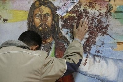 An Egyptian Christian mourns as he stands next to a blood-stained painting of Jesus Christ at the Al-Qiddissine (The Saints) church in Alexandria.  (AFP File Photo/Mohammed Abed)