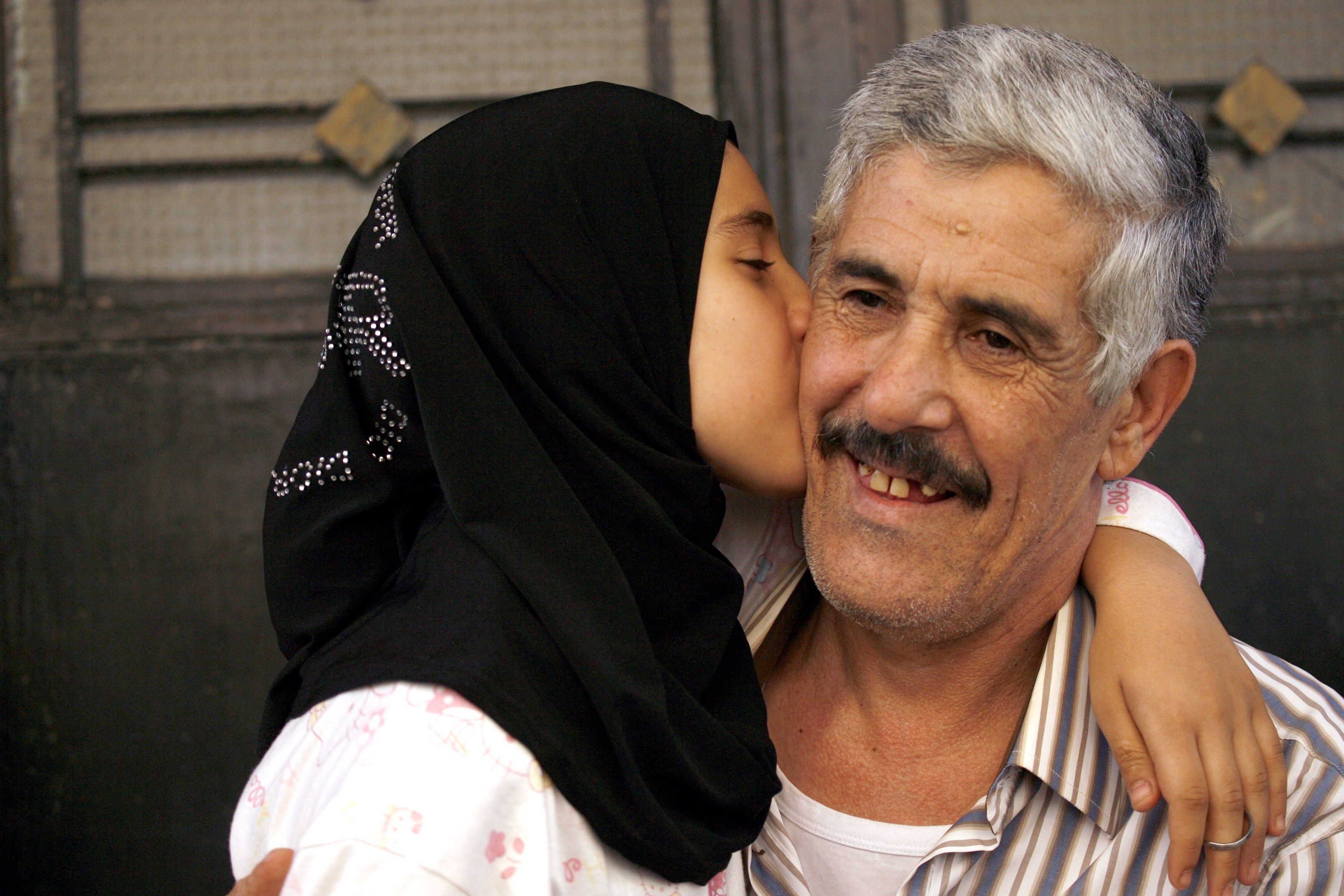 Abbas Hammoud, one of the nine Lebanese pilgrims held hostage in Syria for 17 months, is kissed by his daughter Fatima upon his arrival at his home in the coastal city of Tyre in south Lebanon on Sunday (AFP PHOTO MAHMOUD ZAYYAT)