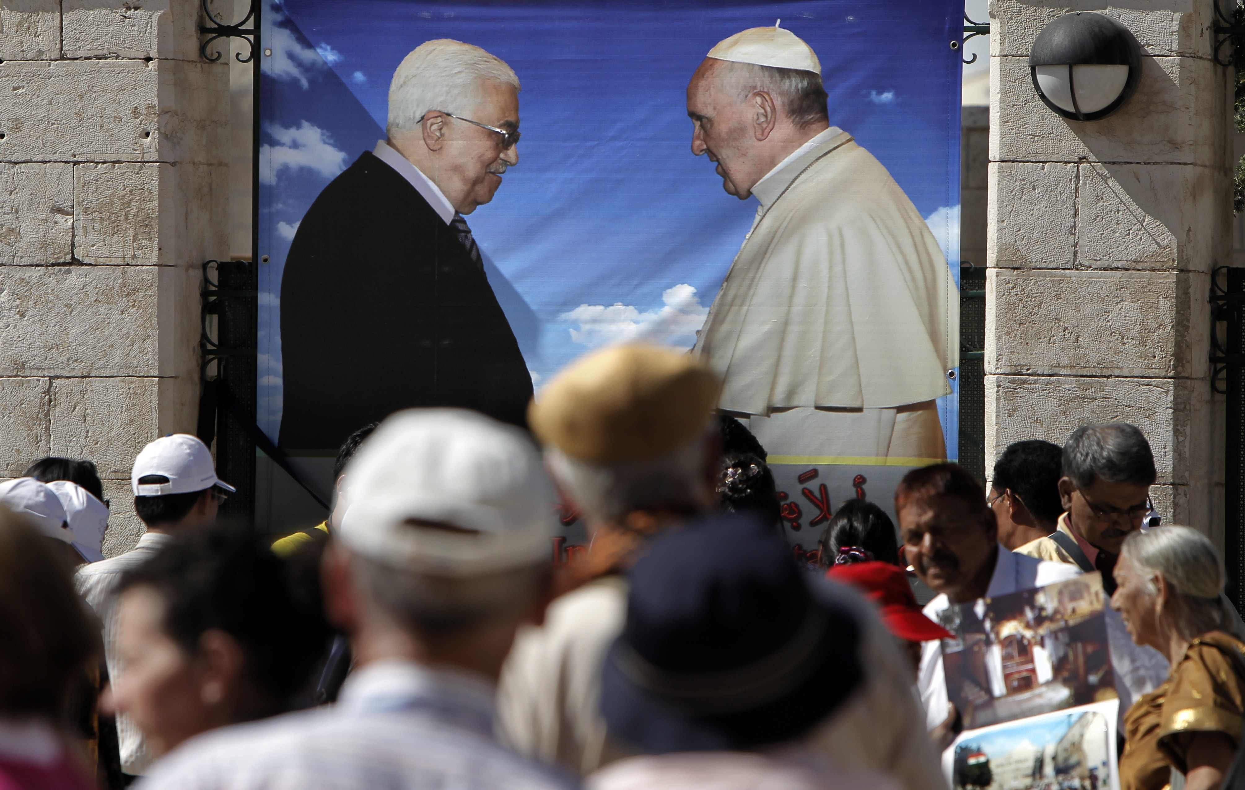 Tourists walk past a banner bearing portraits of Pope Francis and Palestinian Authority president Mahmud Abbas (L), on May 18, 2014, in front of the Church of Nativity, in the West Bank Town of Bethlehem. The pope's visit is scheduled to begin in Jordan on May 24, and he is then due to spend two days in the Holy Land from May 25.  (AFP PHOTO / AHMAD GHARABLI)