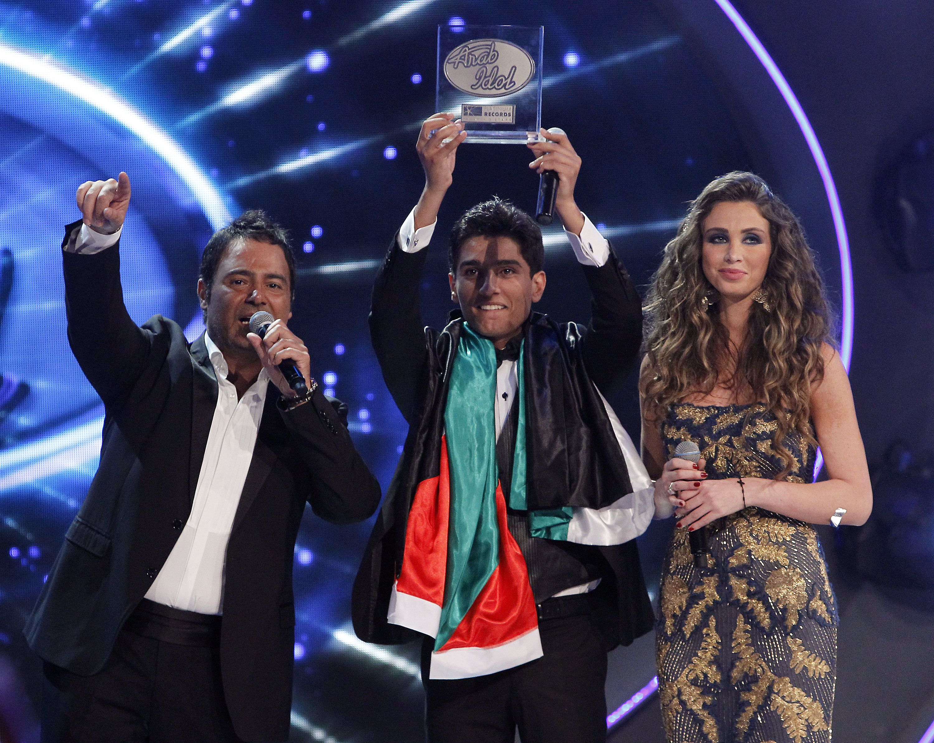 Palestinian contestant Mohammed Assaf (C) raises his trophy next to Lebanese singer Assi al-Hallani (L) and host Annabella Hilal after winning the Arab Idol singing contest in Zouk Mosbeh, north of the Lebanese capital Beirut, early on 23 June (AFP PHOTO/ANWAR AMRO)